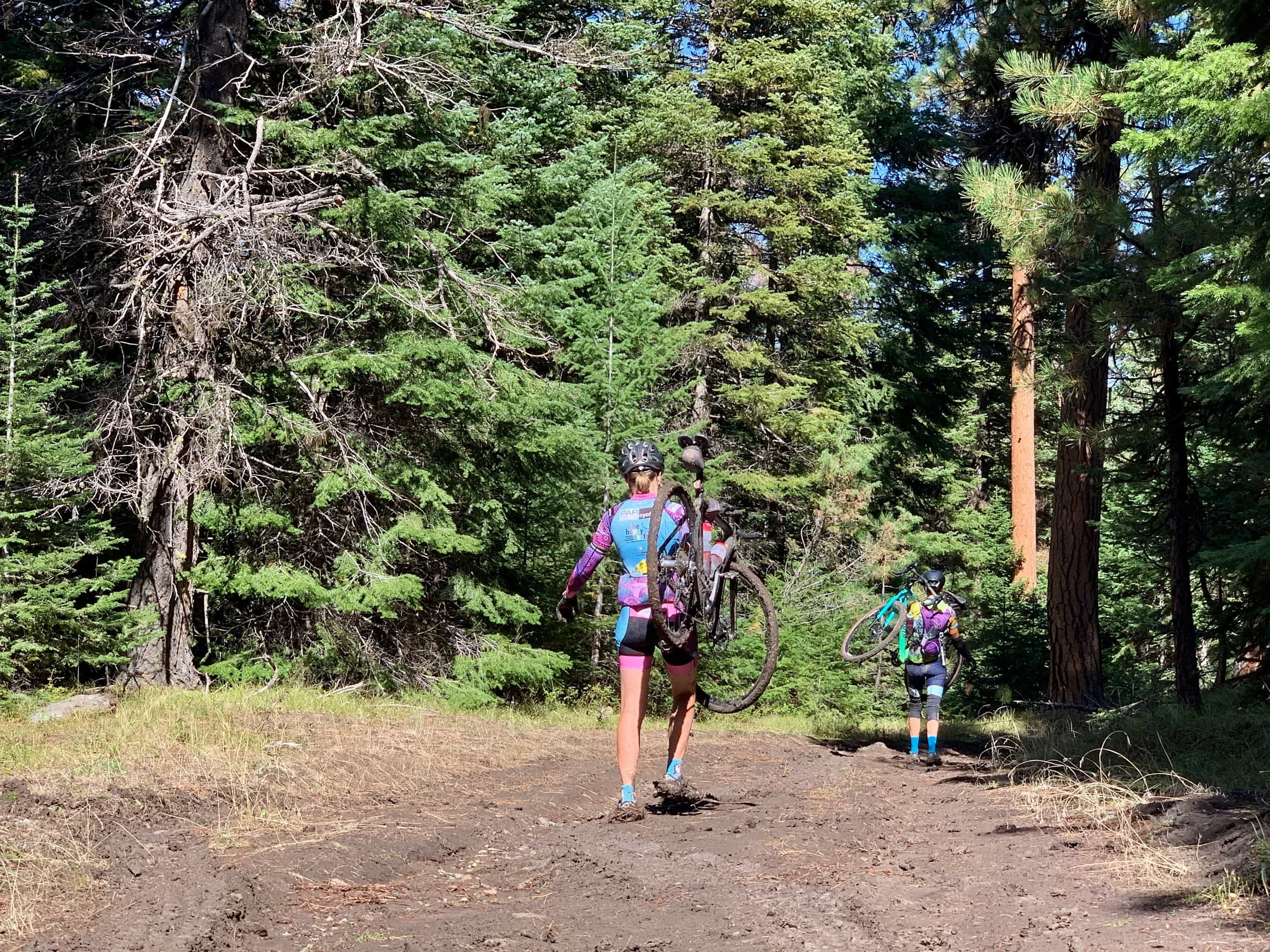 Two gravel girls carrying bikes through muddy / boggy road in Ochoco mountains.