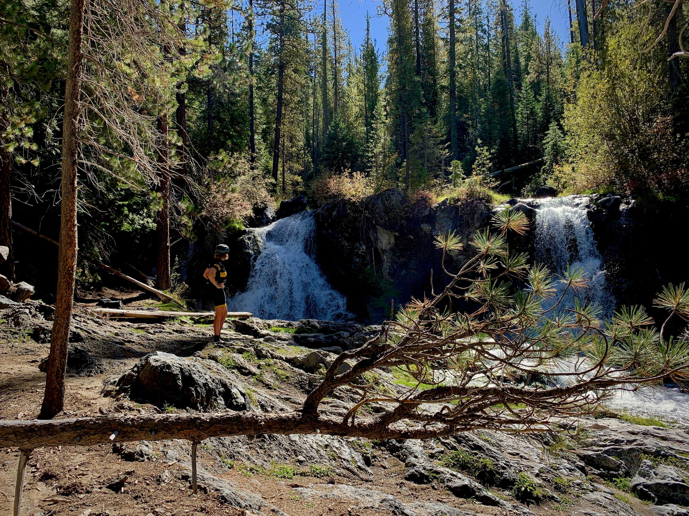 Cyclist standing next to split falls along Paulina creek in Newberry National Volcanic Monumnent.