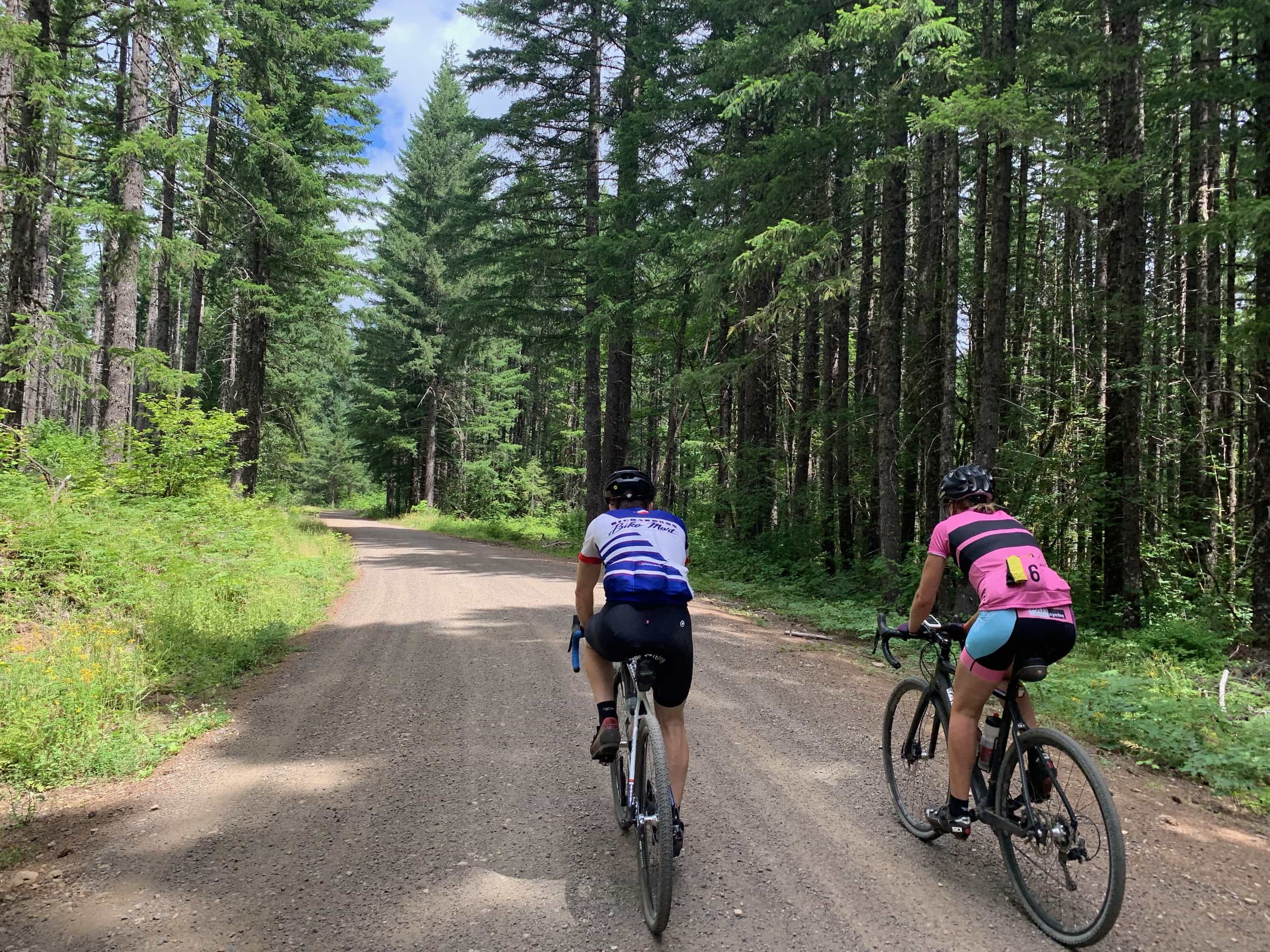 Two bike riders on gravel road approaching NF-66 near Stabler, Washington.