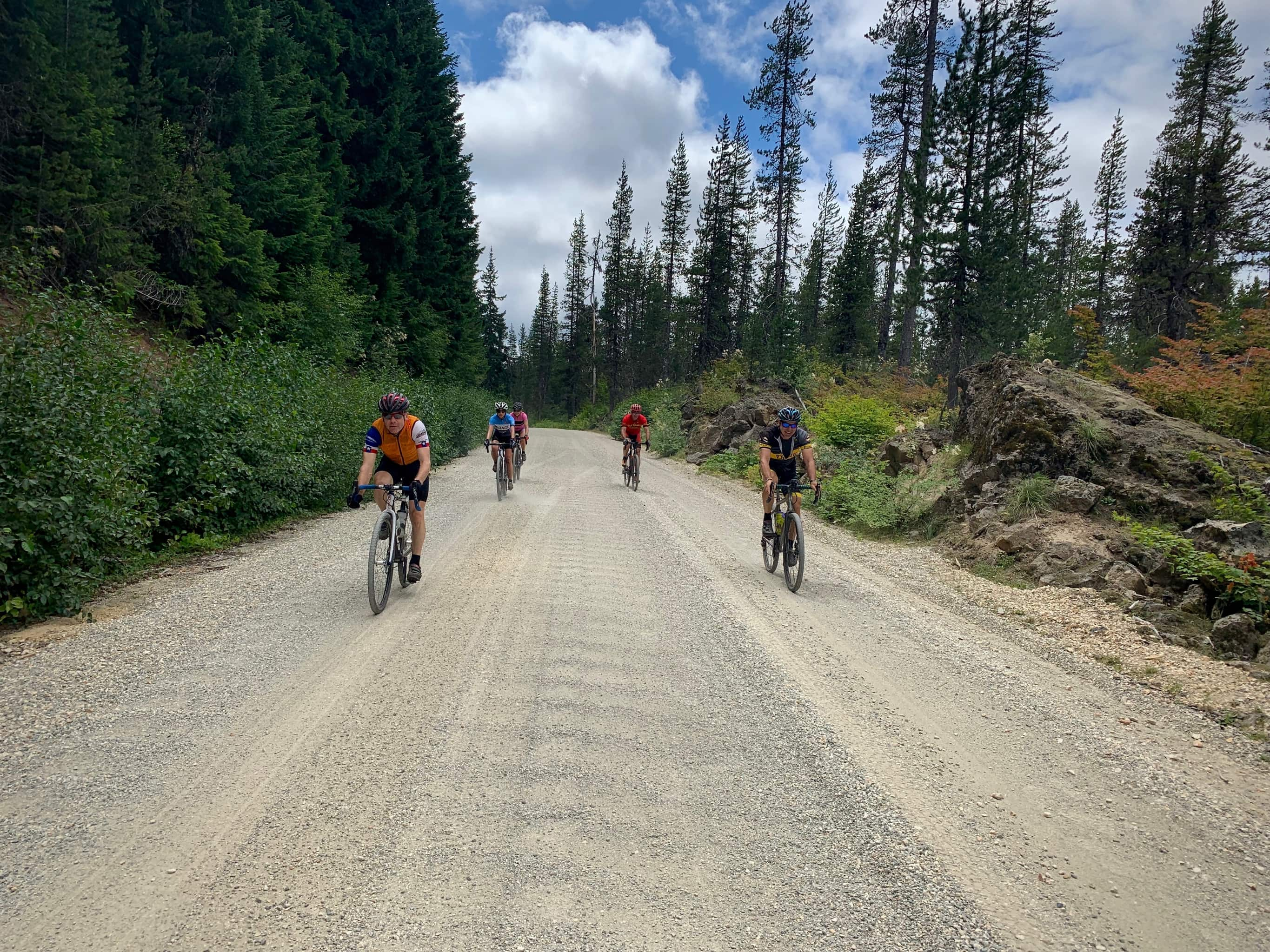 Cyclists on gravel road approaching South Prairie and the disappearing lake in the Gifford Pinchot National Forest.