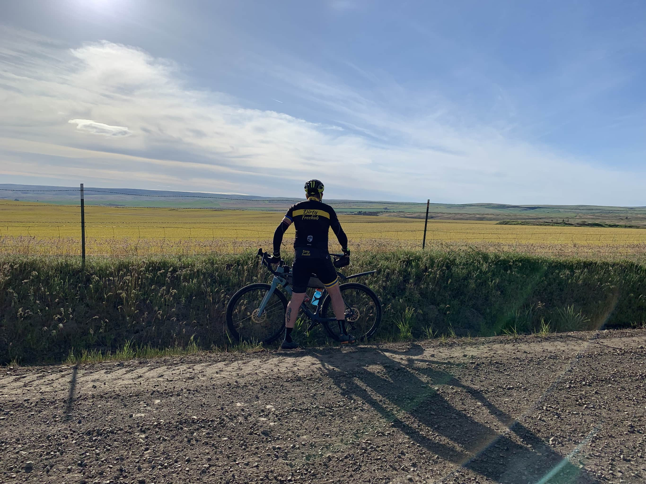 Cyclist looking over wheat and hay fields between Dufur and Tygh Valley, Oregon.