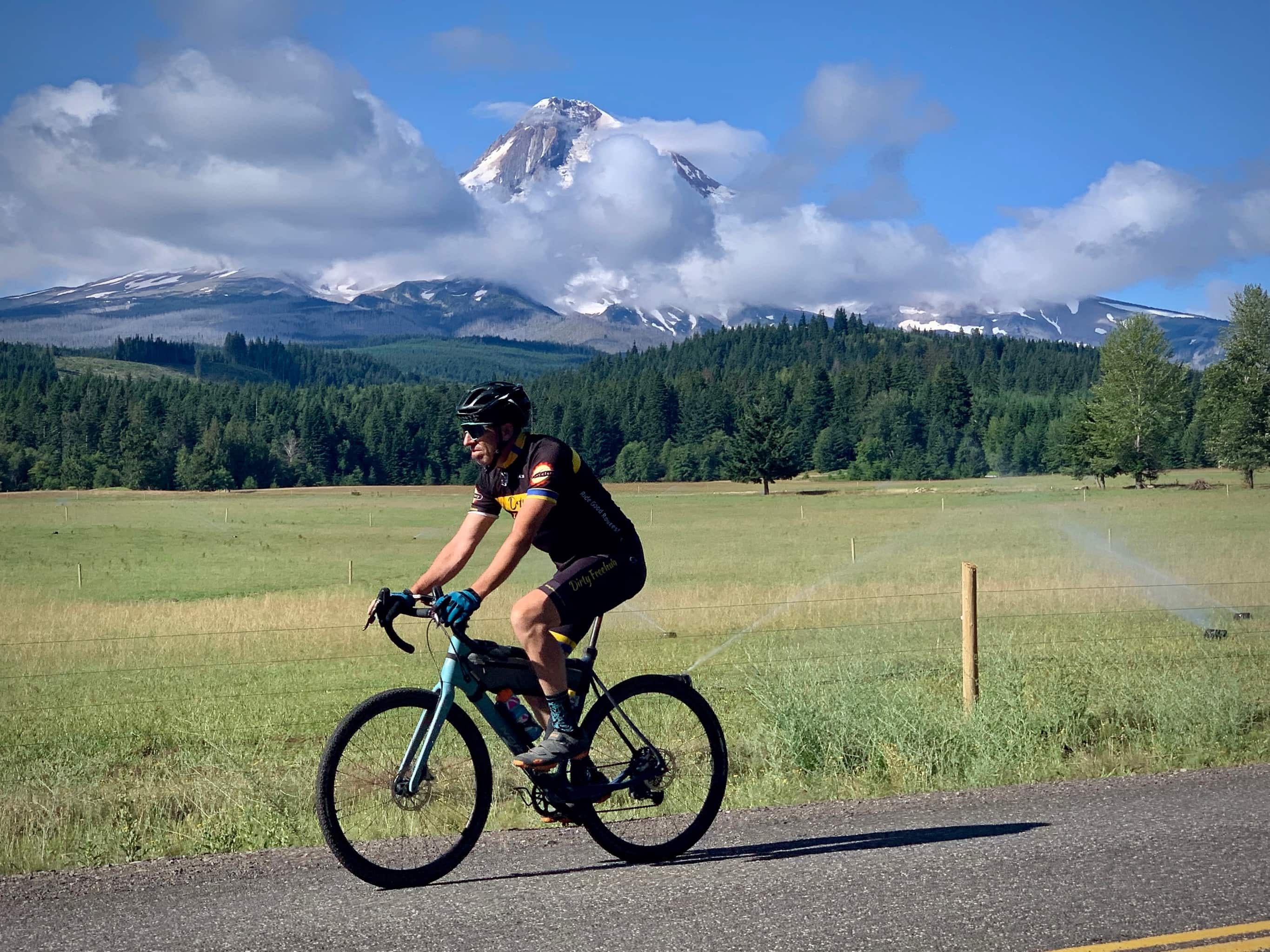 Cyclist on paved road with Mt. Hood in the background, near Parkdale, Oregon.