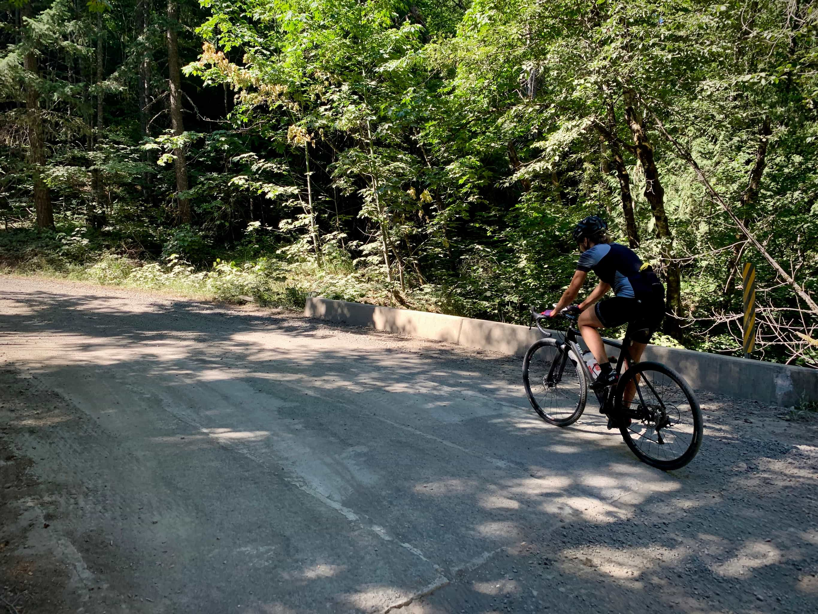 Cyclist on gravel road crossing over Dead Point creek in Hood River county.