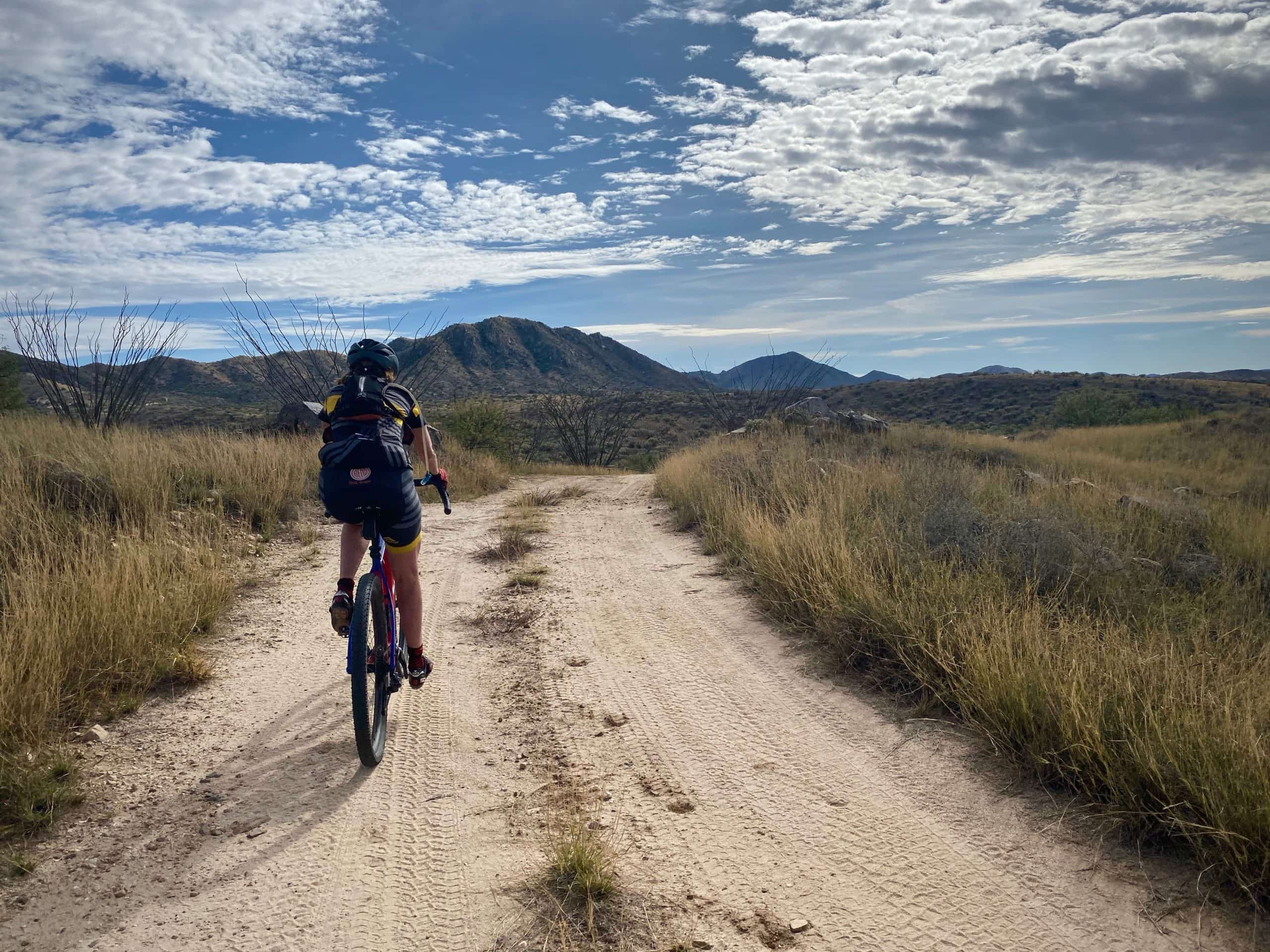 Gravel cyclist on dirt road with Coches Ridge in the background in Buenos Aires National Wildlife Refuge in Arizona.