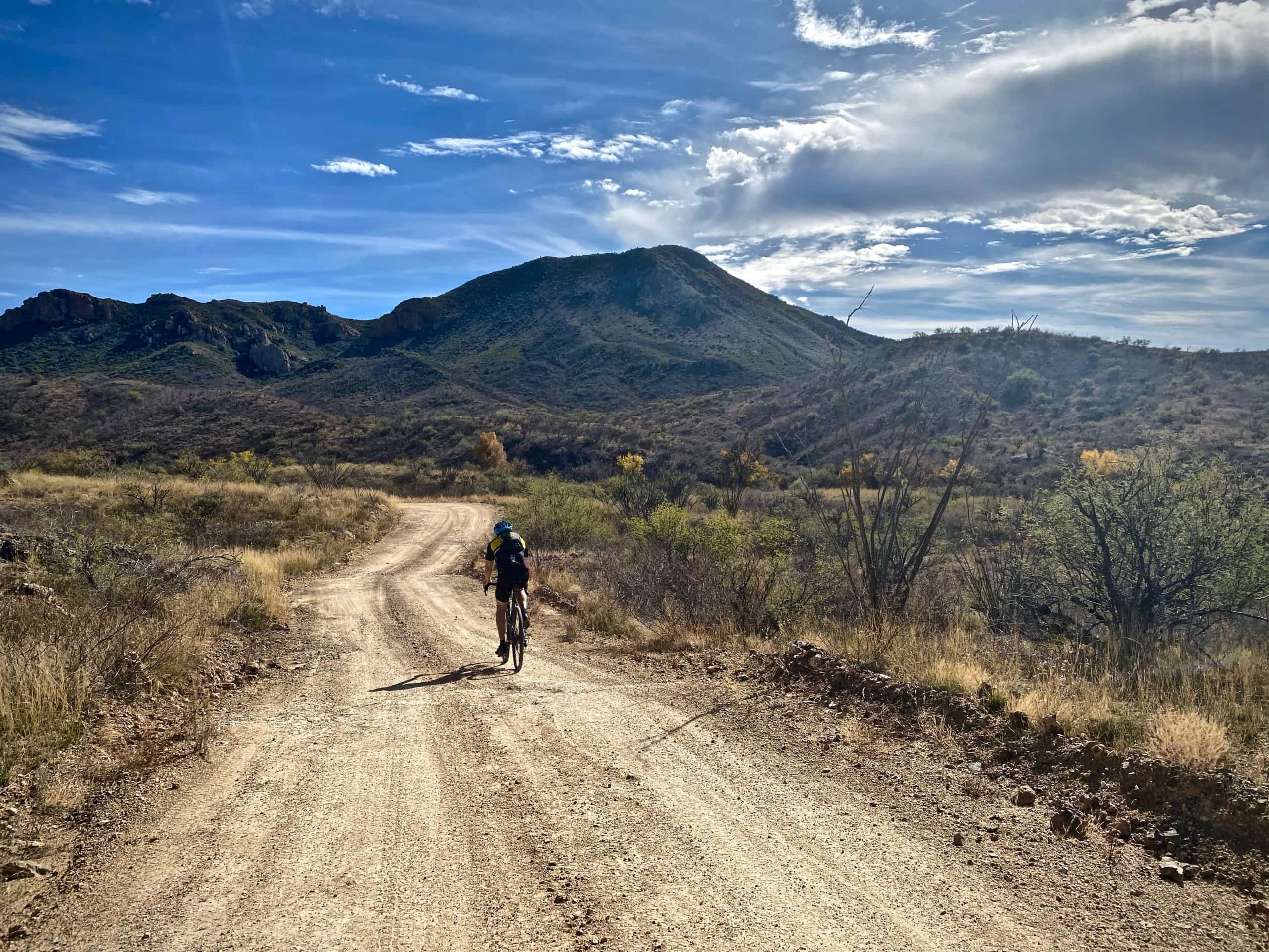 Gravel cyclist in Buenos Aires National Wildlife Refuge riding through thorn-scrub.