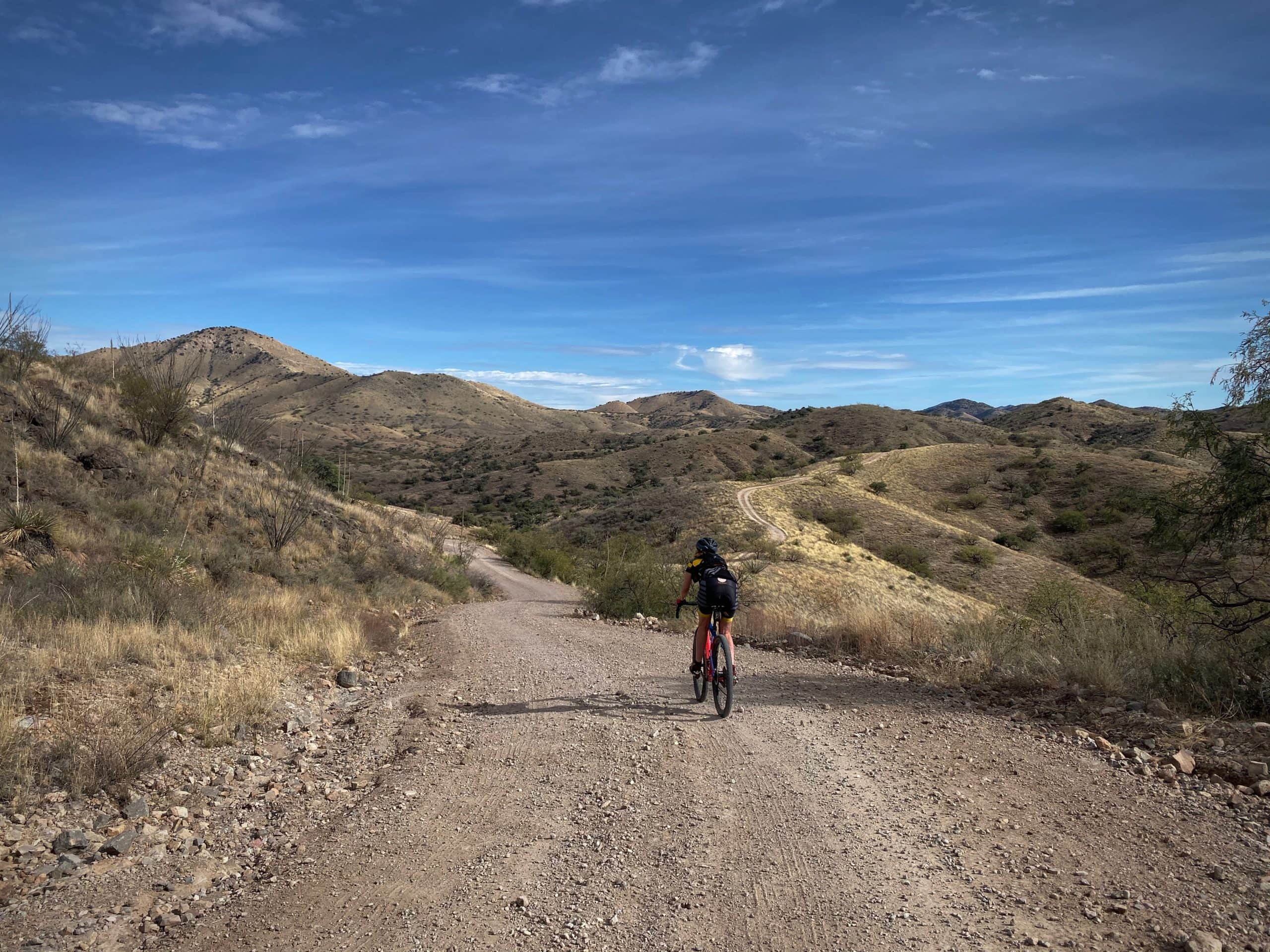 Woman gravel cyclist on rolling hills in Buenos Aries National Wildlife Refuge.