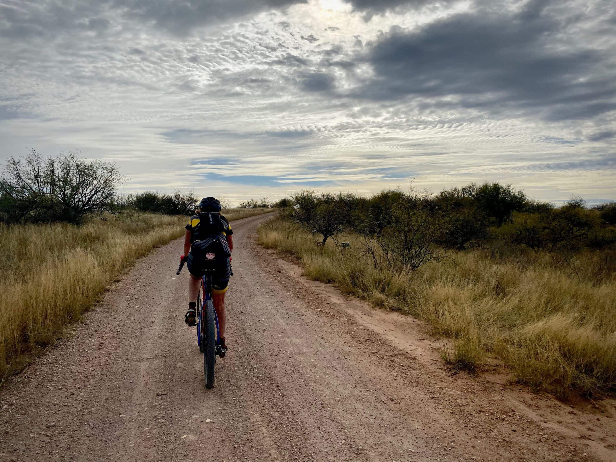 Cyclist riding the gravel / dirt roads in the grasslands of Buenos Aires National Wildlife Refuge.