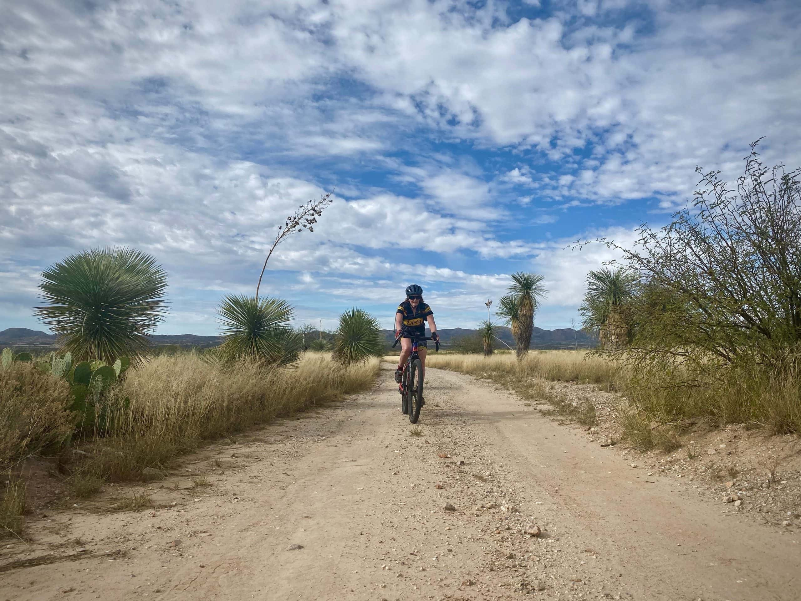 Woman gravel cyclist riding between yucca plants in Buenos Aires National Wildlife Refuge near Arivaca, Arizona.