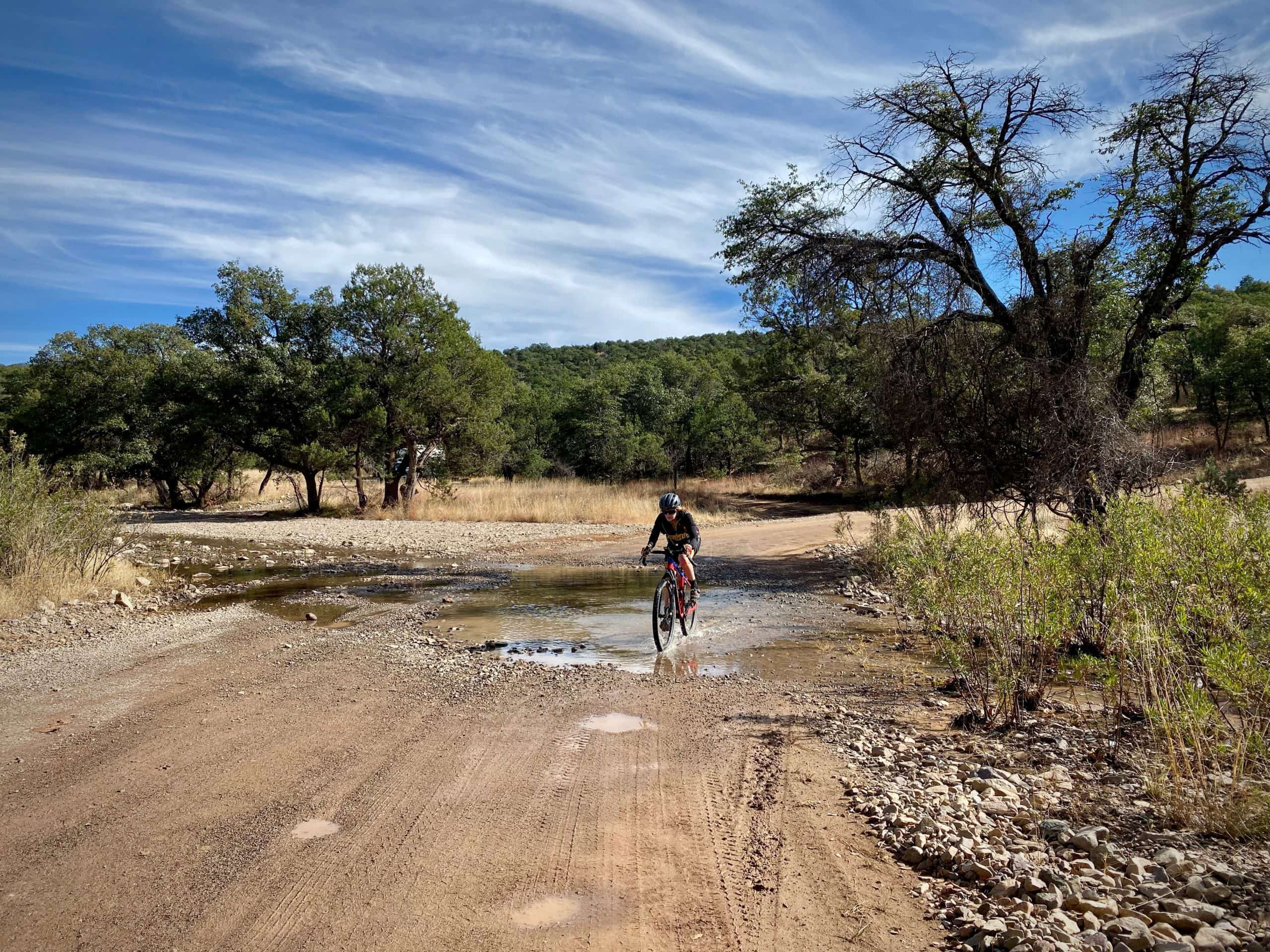 Cyclist riding through a wash with running water in the San Rafael Valley near Patagonia, Arizona.