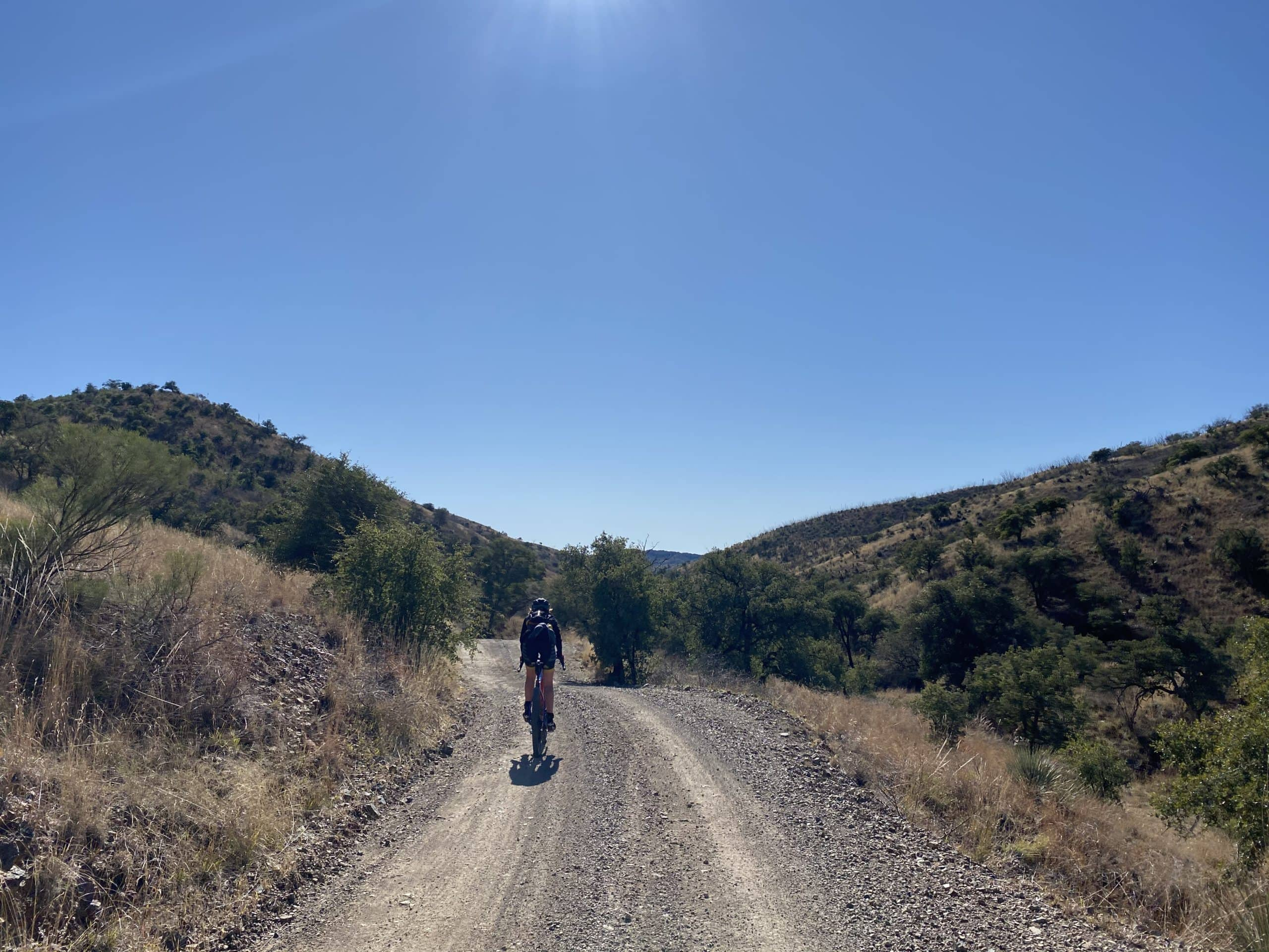 Woman gravel cyclist riding along Warsaw creek in the Coronado National Forest.