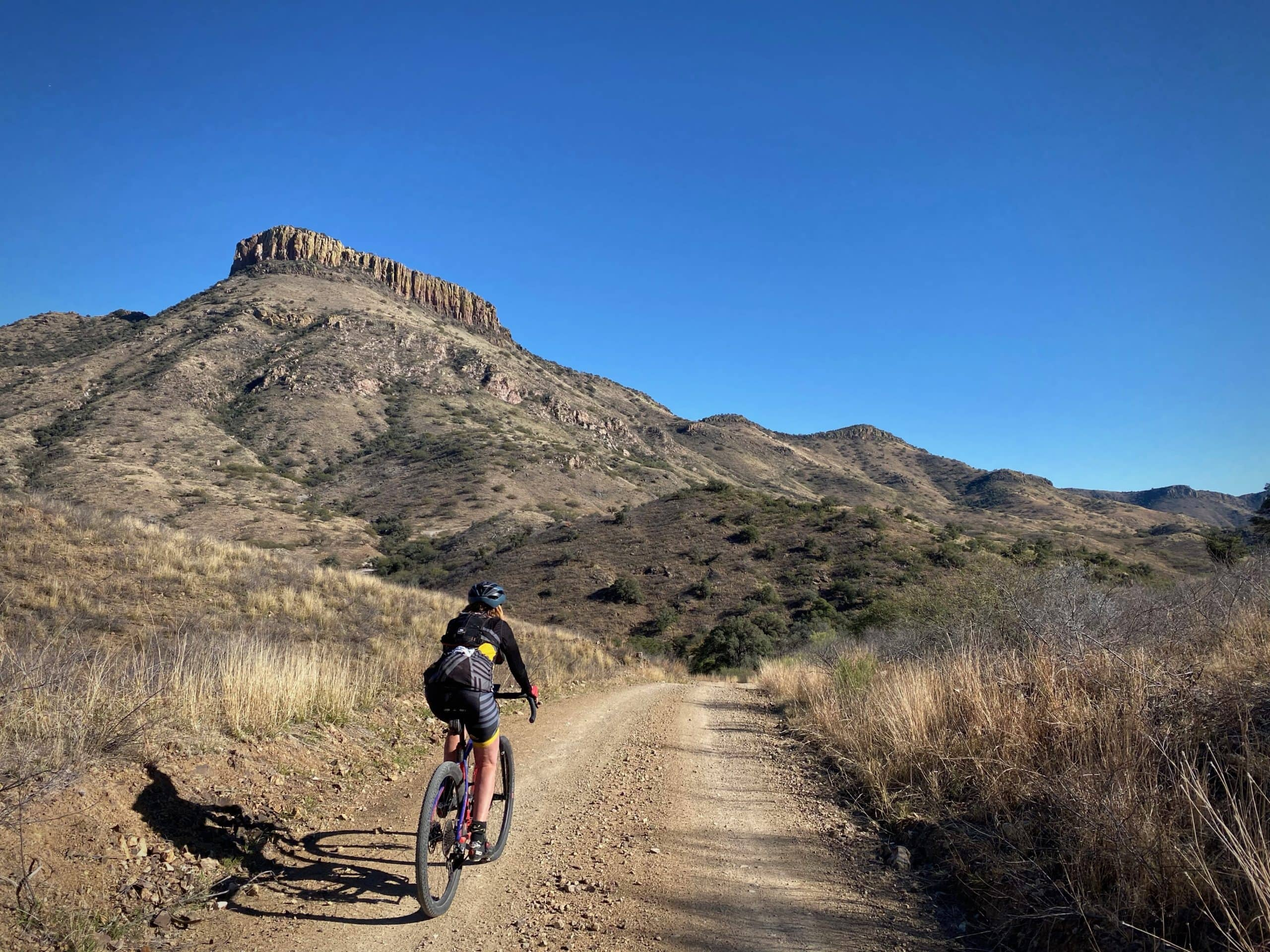 Cyclist on gravel road with Bartolo Mountain in the background.