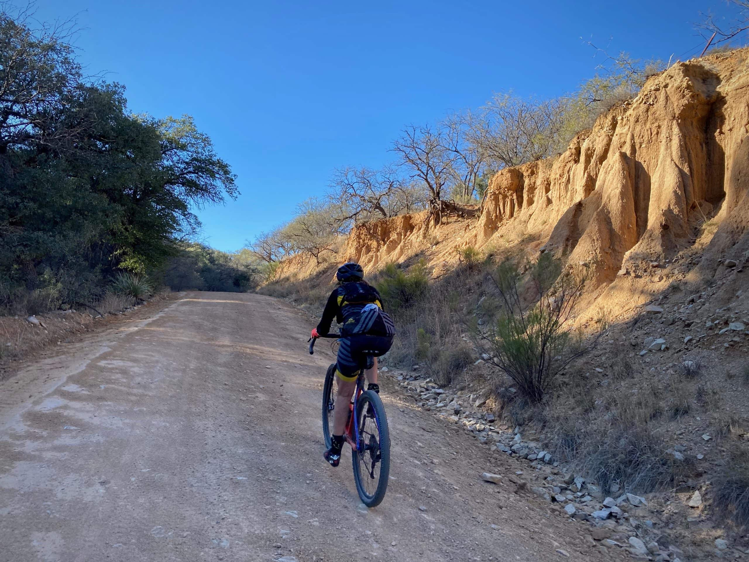 Woman gravel cyclist on gravel road in Oro Blanco wash in the Coronado National Forest.