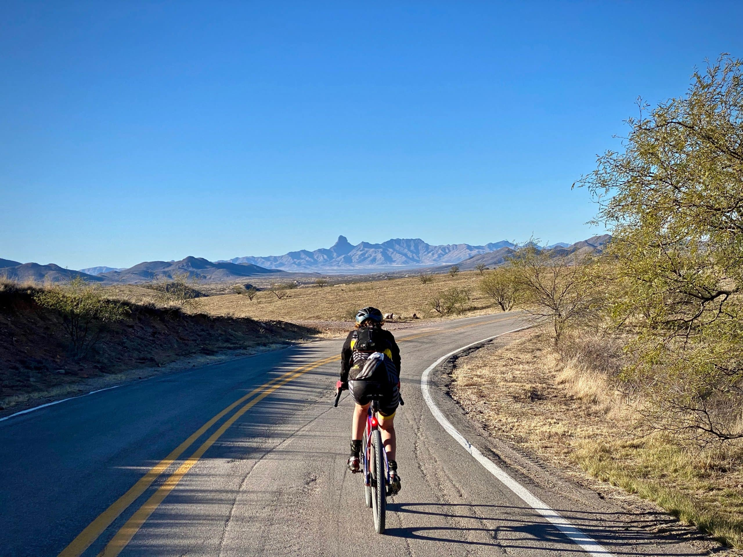 Cyclist on Ruby road with Baboquivari Peak in the background.