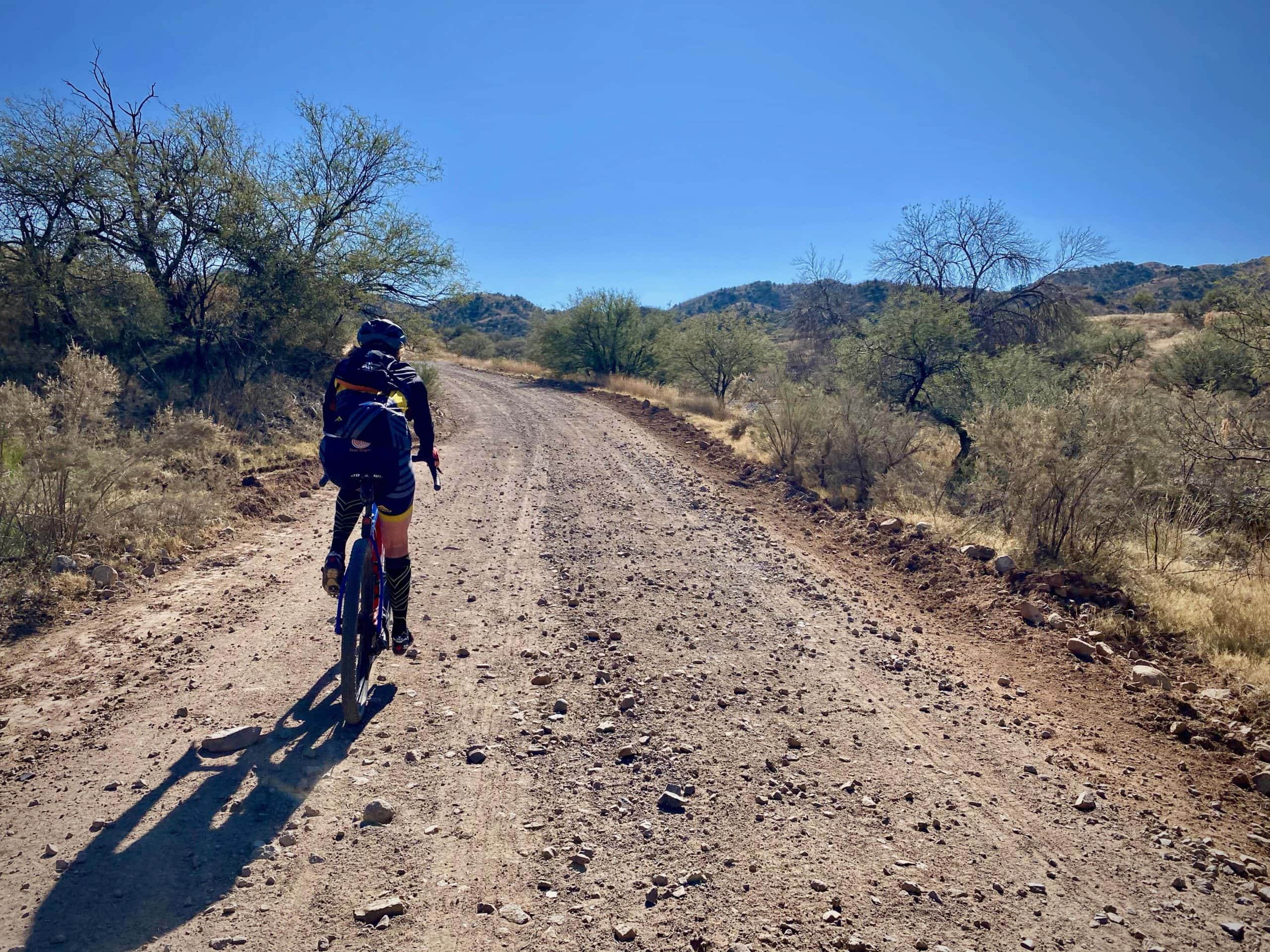 Cyclist on the gravel portion of Ruby Road in the Coronado National Forest.