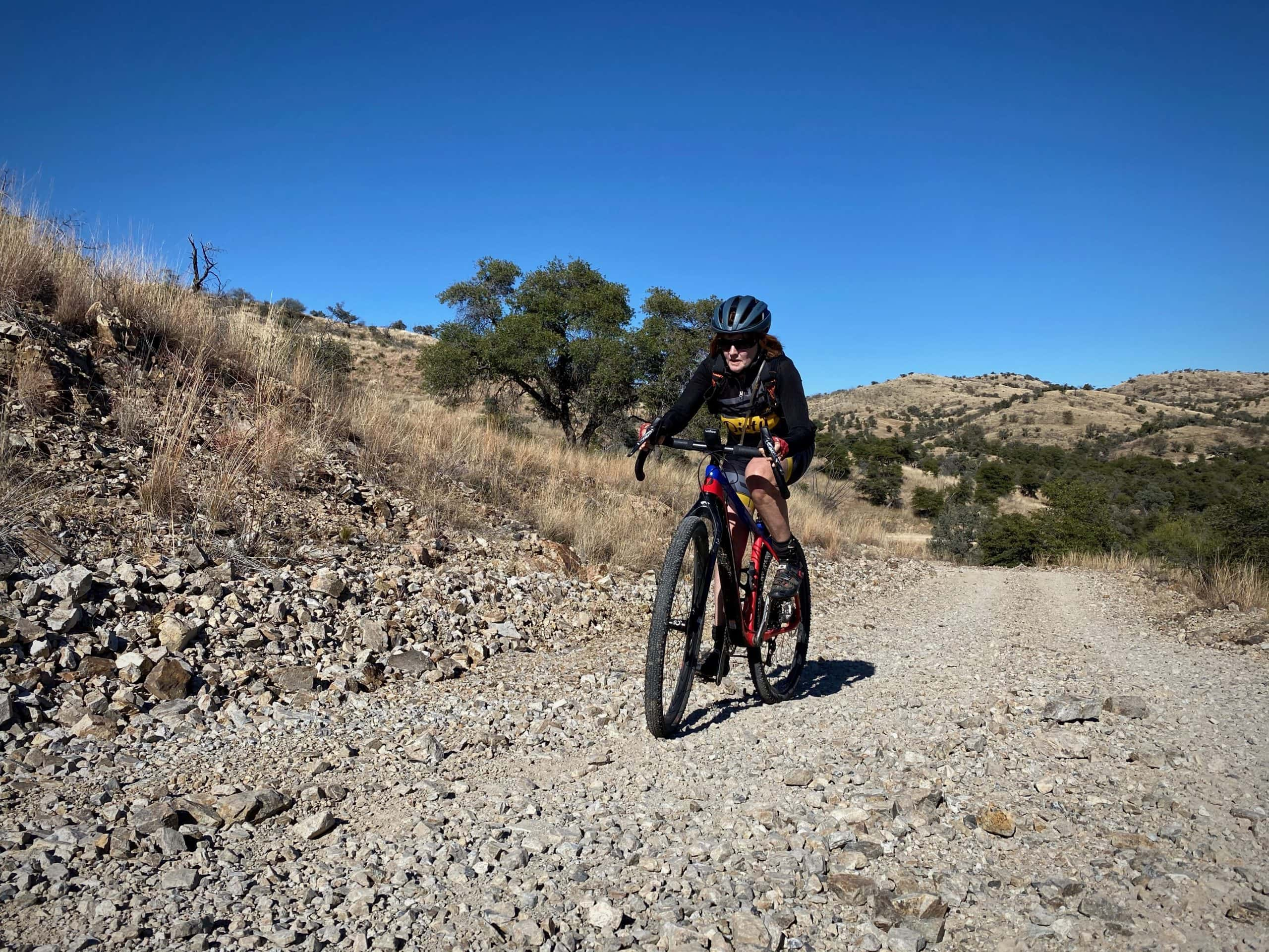 Gravel cyclist climbing hill on FS 217 in Warsaw Canyon.