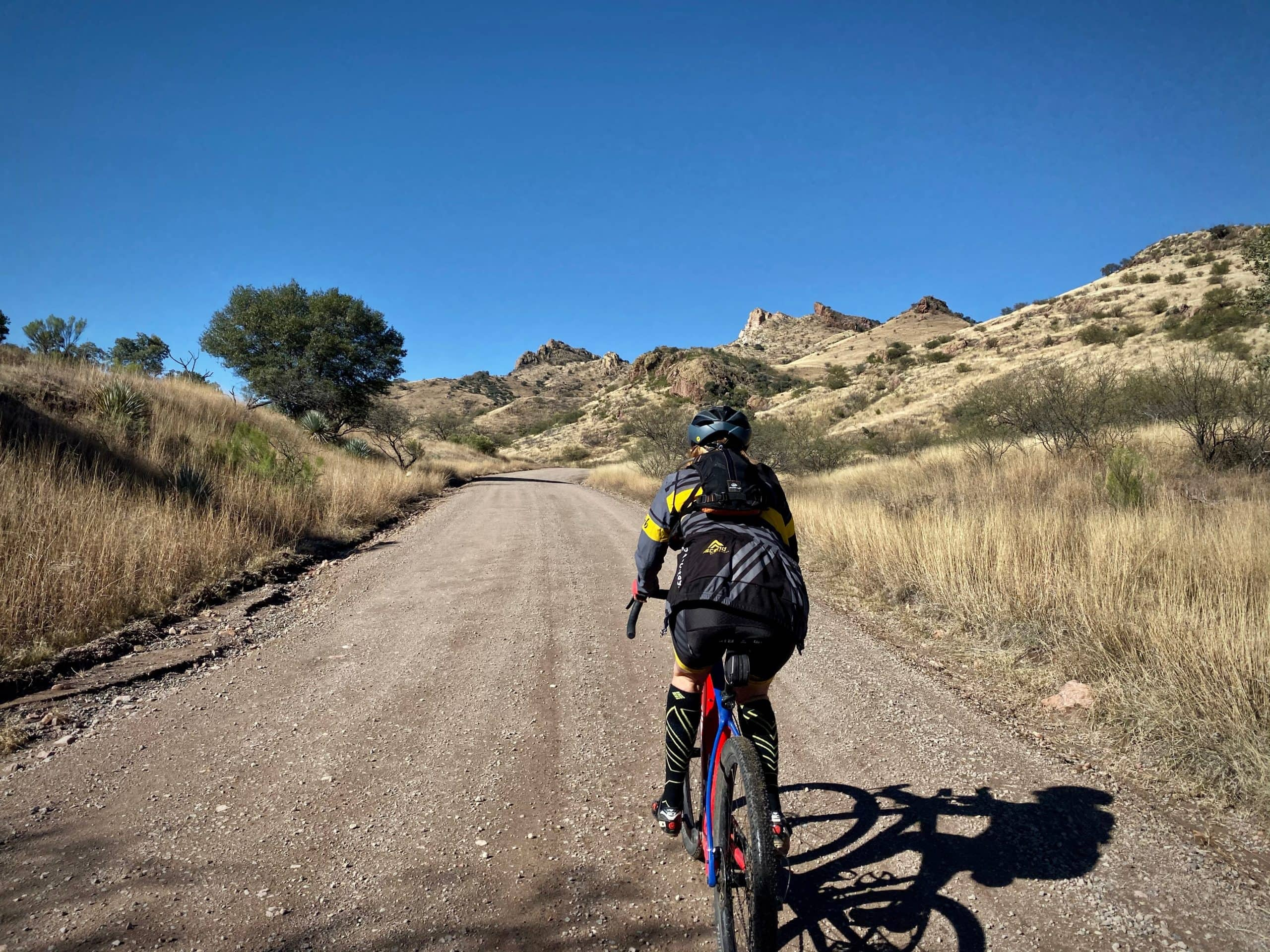 Gravel cyclist climbing Ruby Road from the south near Pena Blanca wash.