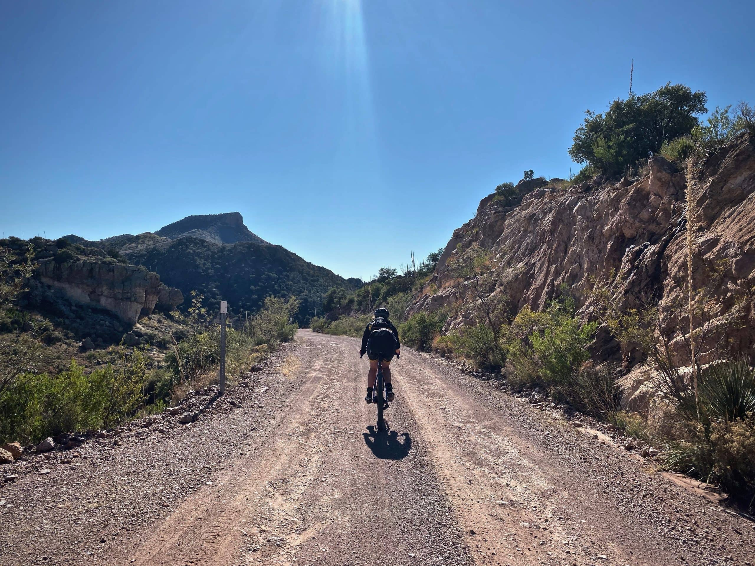 Cyclist on gravel road approaching Montana Peak in southern Arizona.
