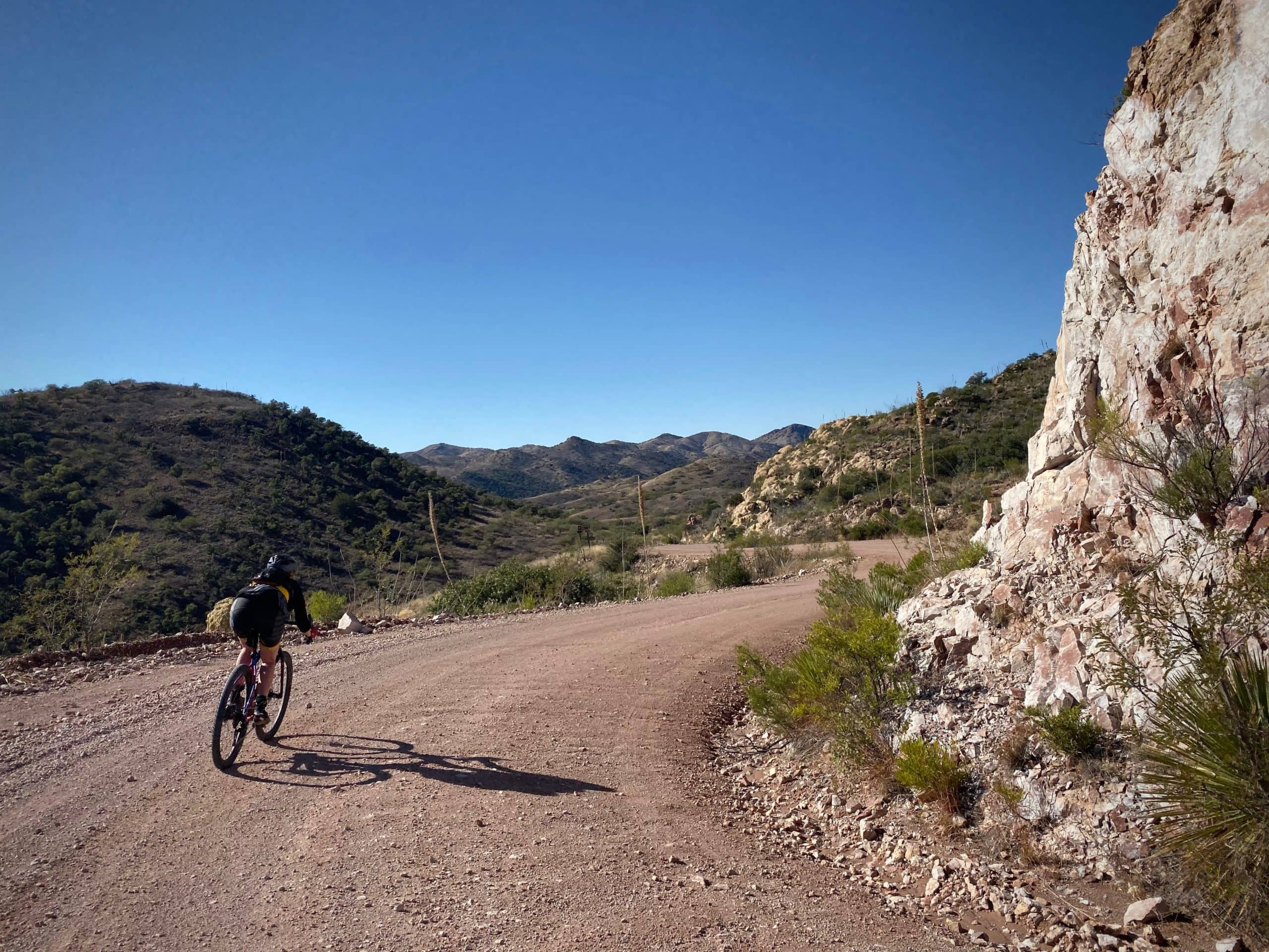Cyclist on Ruby road, gravel, approaching the ghost town of Ruby in the Coronado National Forest.