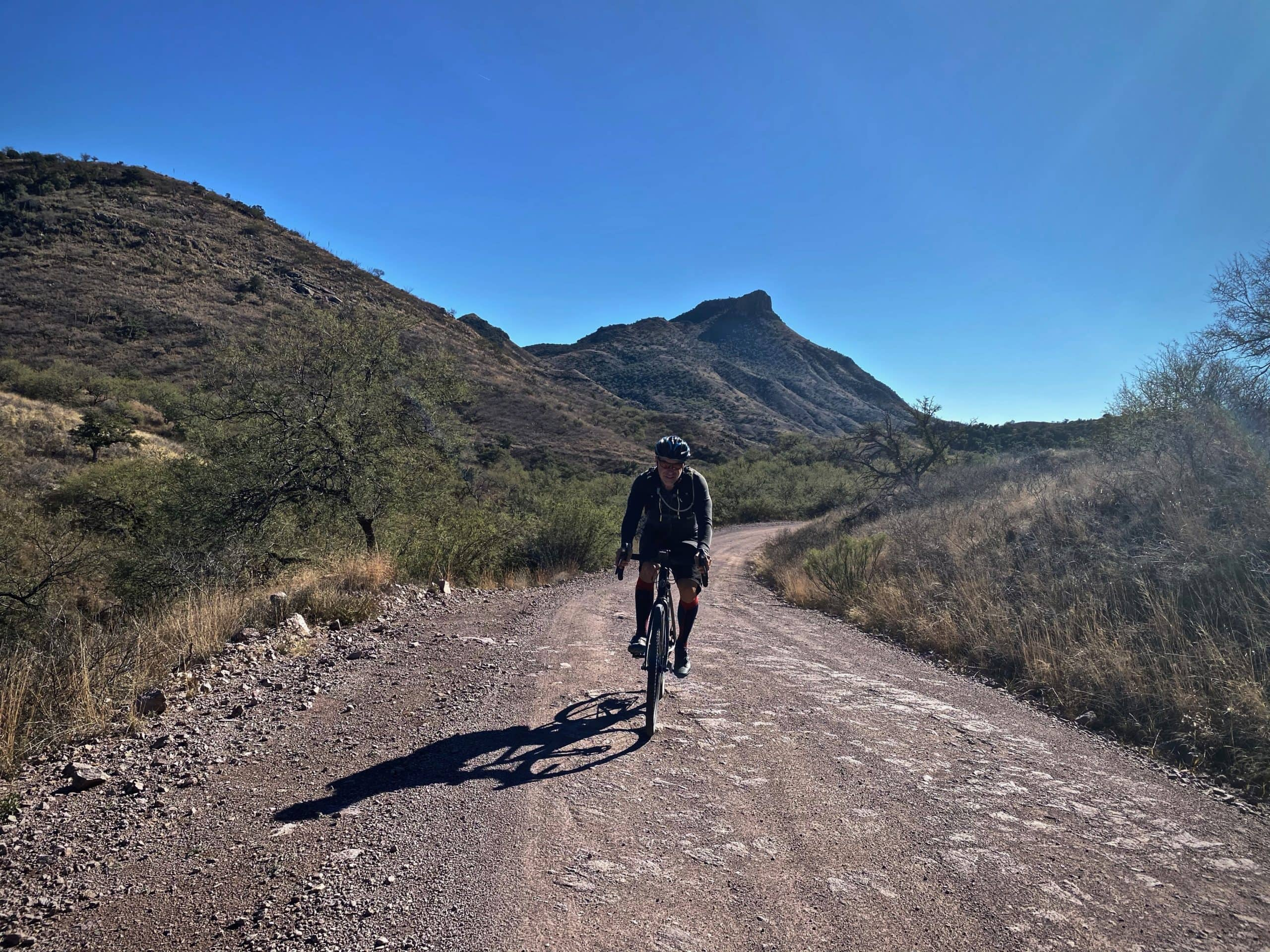 Gravel cyclist on Ruby road with Montana Peak in the background, south of Tucson, Arizona.