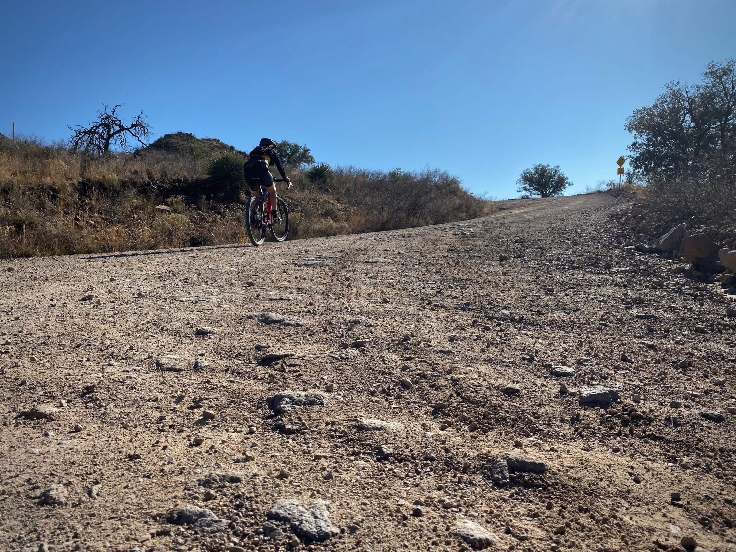 Gravel cyclist on the rough, rock cobbled, section of Ruby road near Nogales, Arizona.