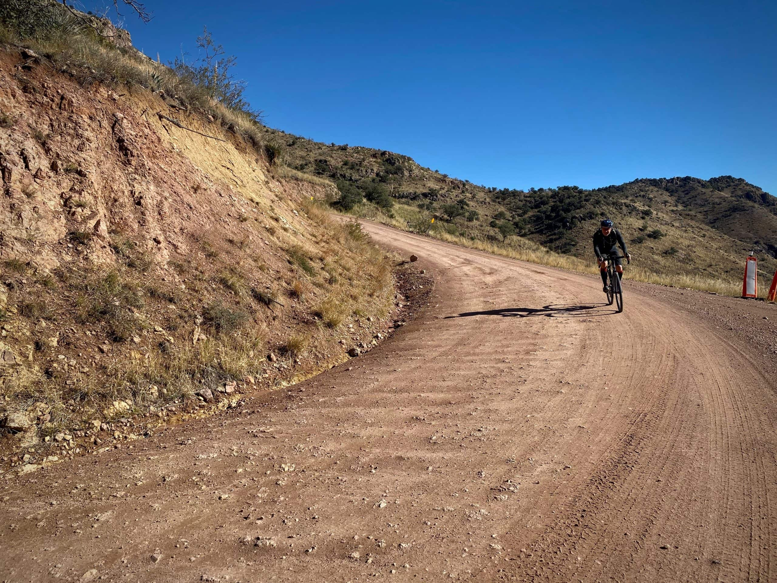 Woman cyclist descending gravel, Ruby road, with some washboard in the Coronado National Forest.