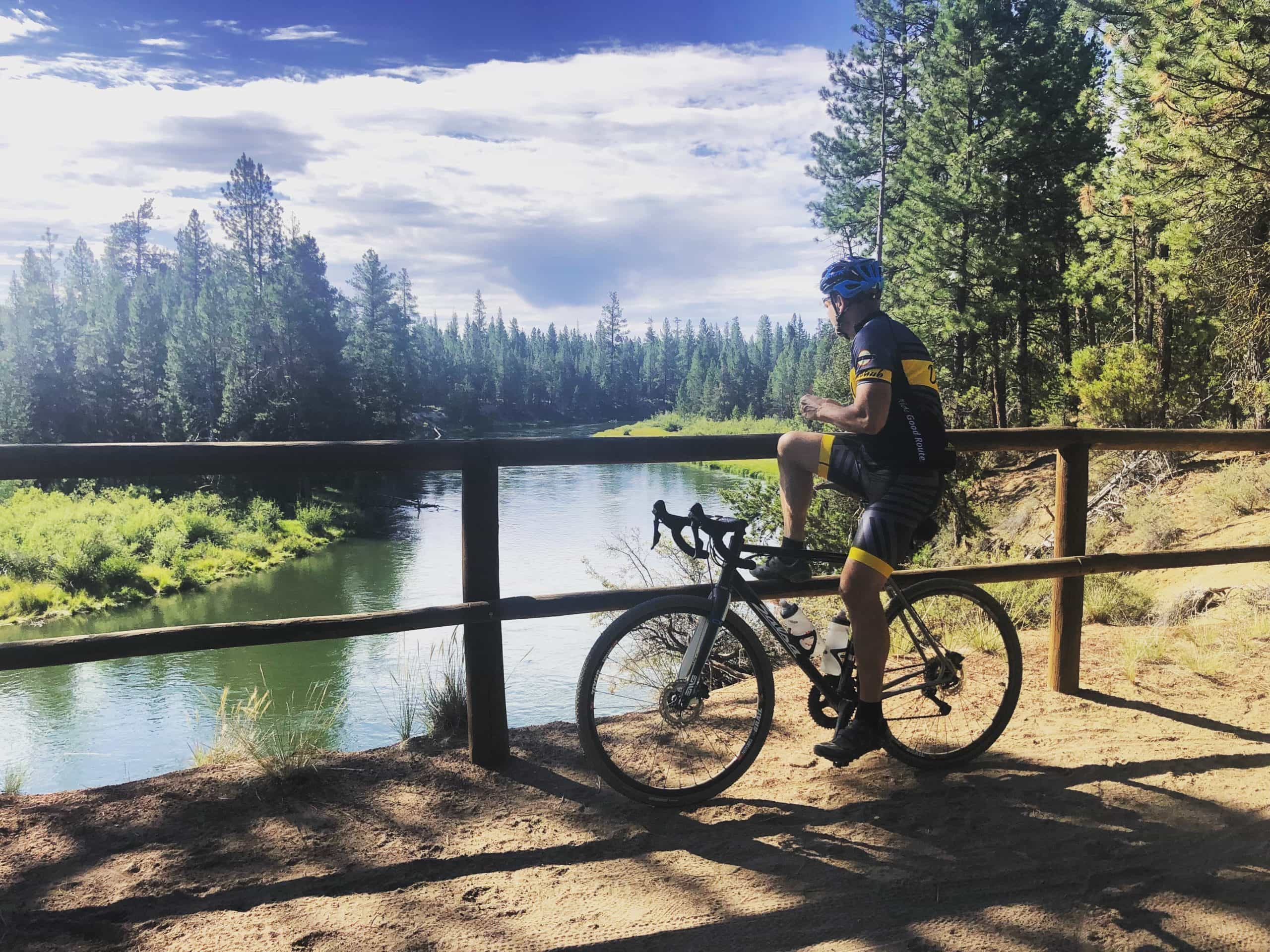 Cyclist looking at Deschutes River from overlook in LaPine State park near Sunriver, Oregon,