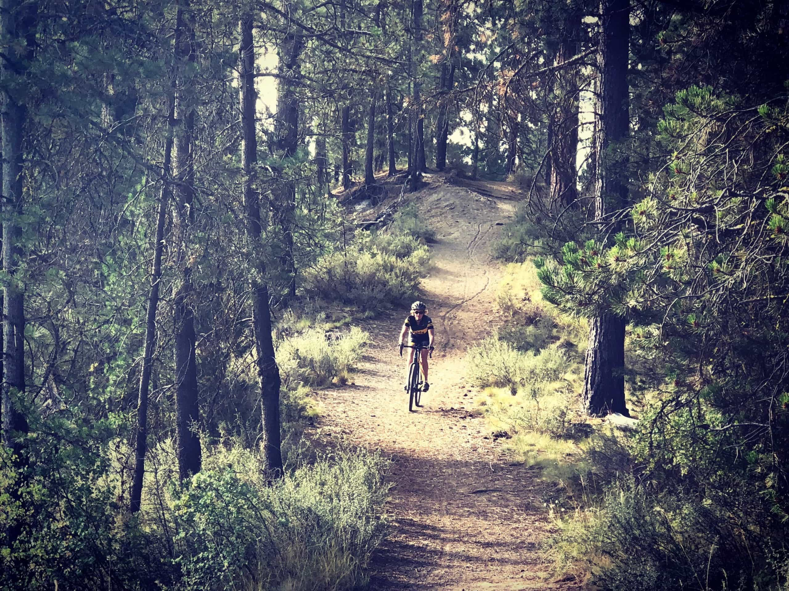 Woman gravel cyclist on dirt trail in LaPine State Park near Sunriver, Oregon.
