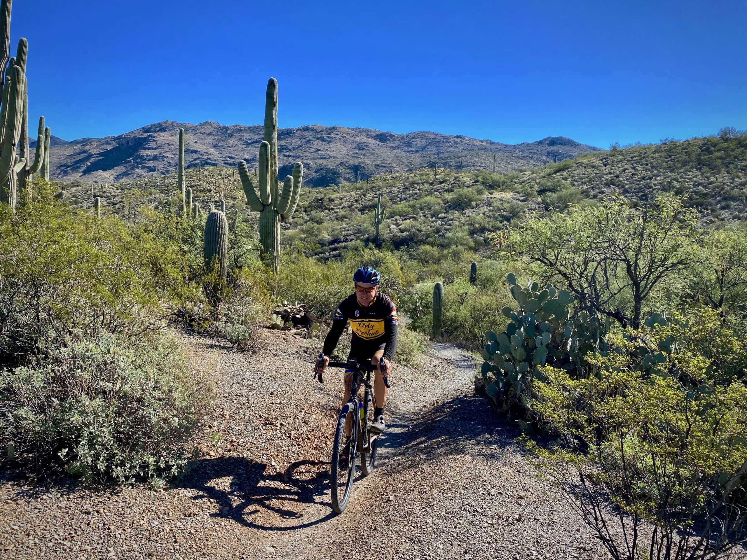 Woman cyclist on Cactus Forest trail with saguaro cactus in background.