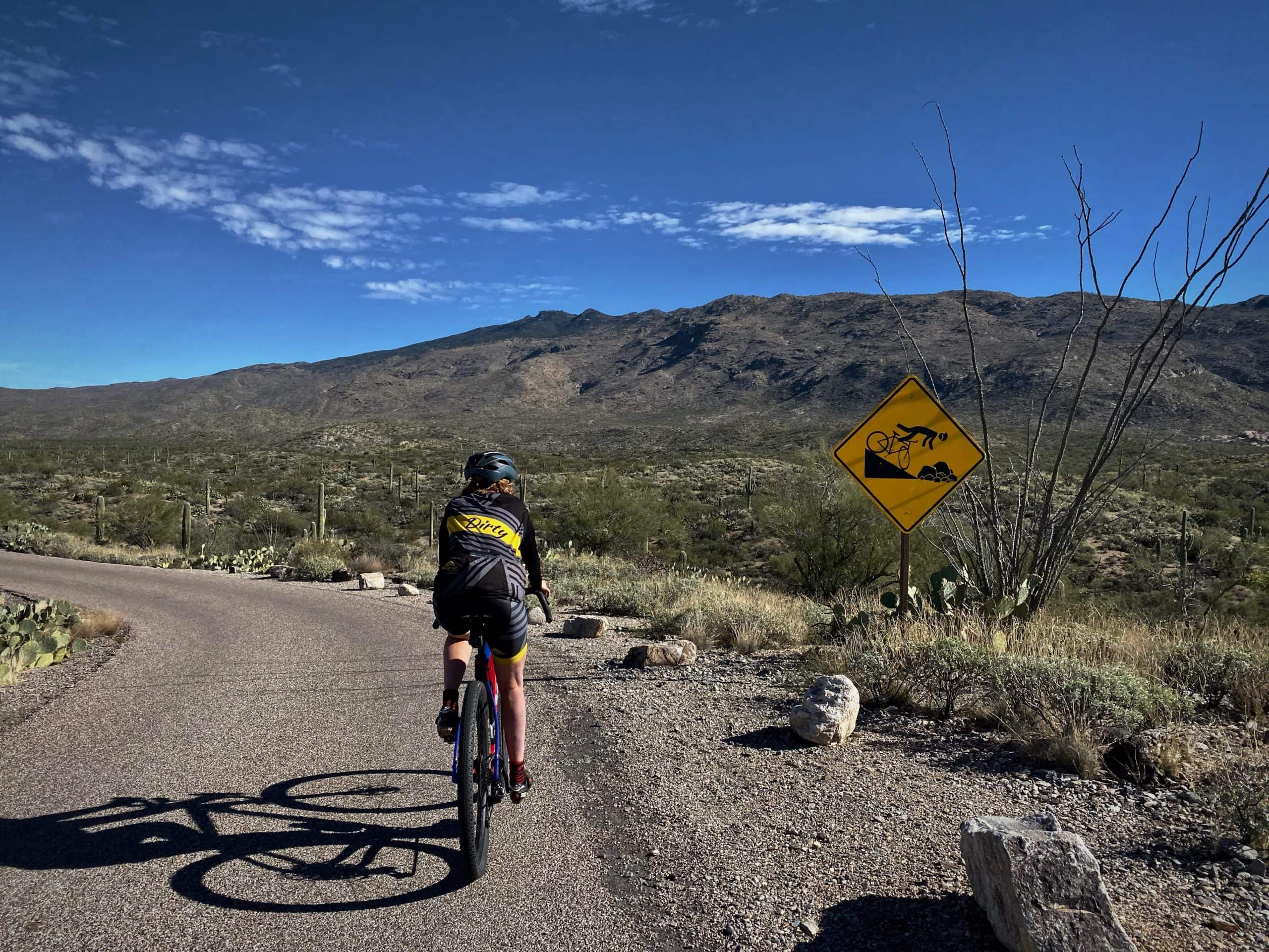 Cyclist on gravel bike on the rollercoaster section of the Cactus Forest road in Saguaro National Park (east).