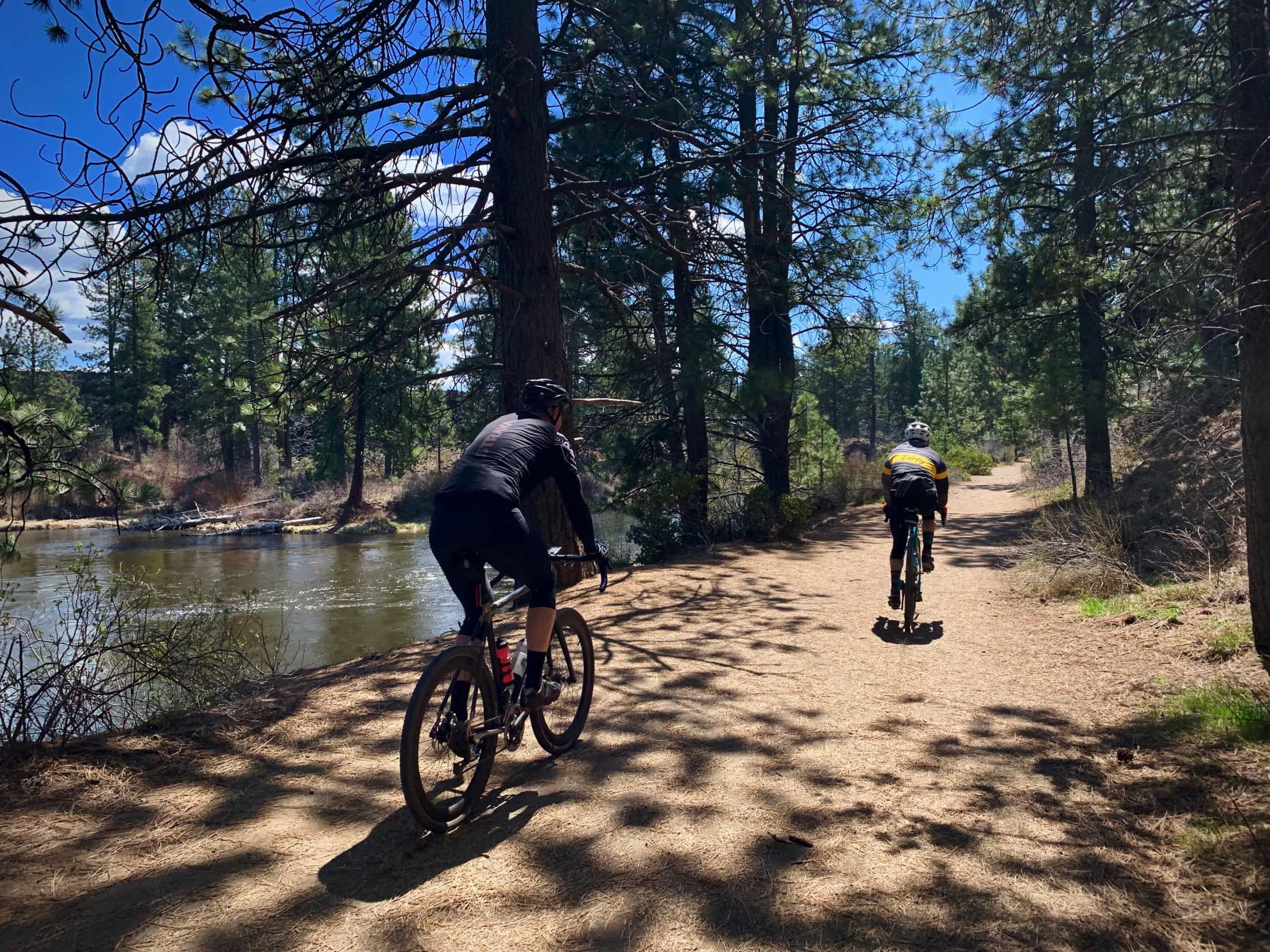 Two cyclists on dirt path between Benham Falls and the wooden bridge over the Deschutes River.