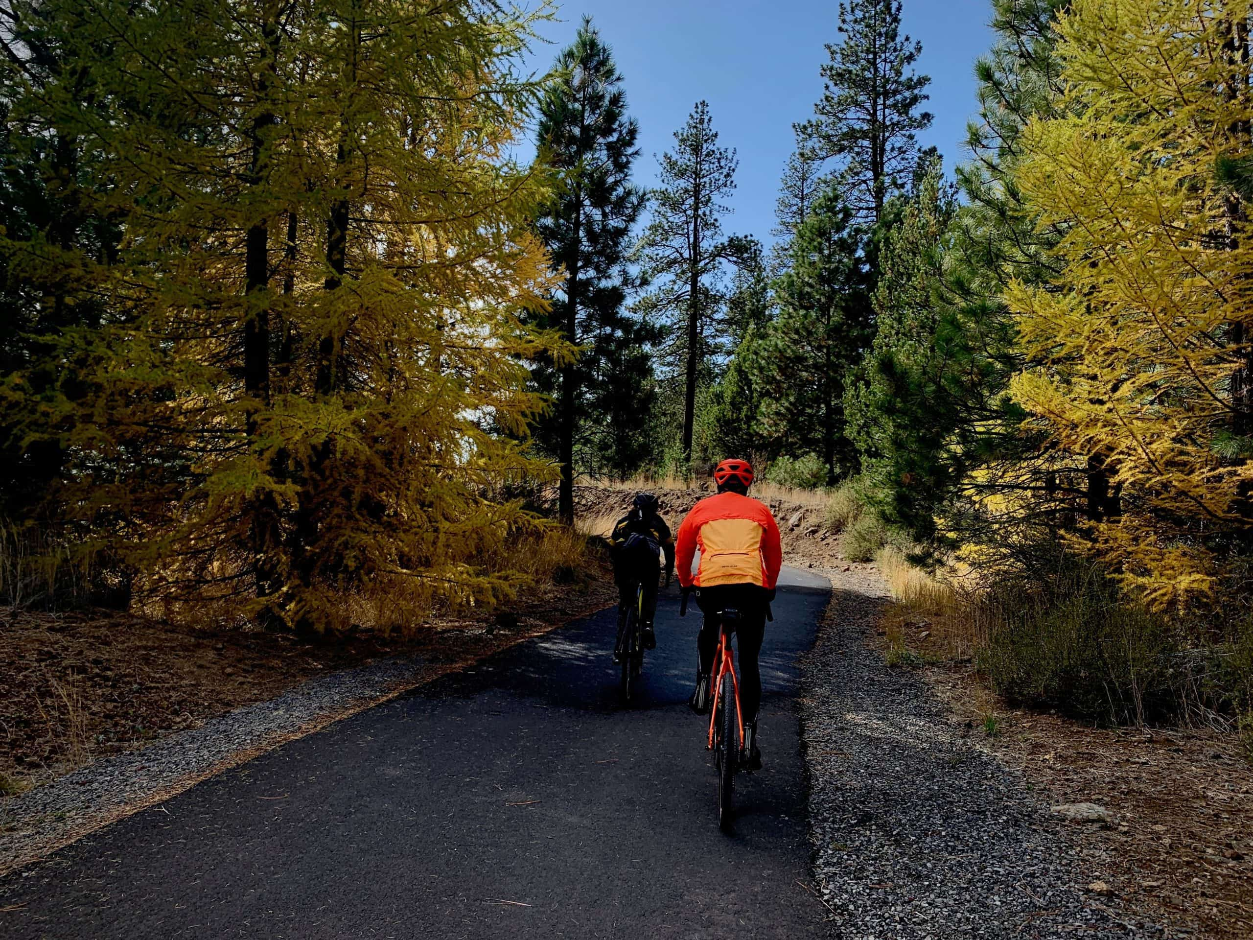 Two cyclists on gravel bikes riding the paved path to Lava Lands Visitor center near Sunriver, Oregon.
