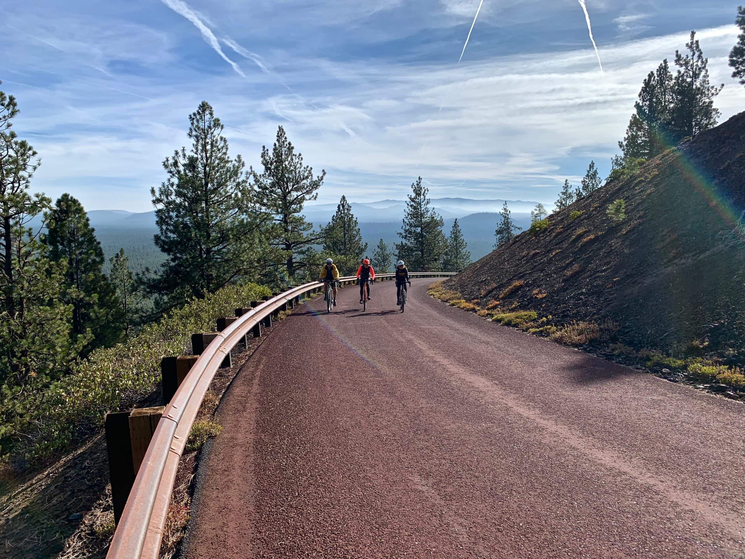 Two women cyclists on gravel bikes climbing to the top of Lava Butte near Bend, Oregon.