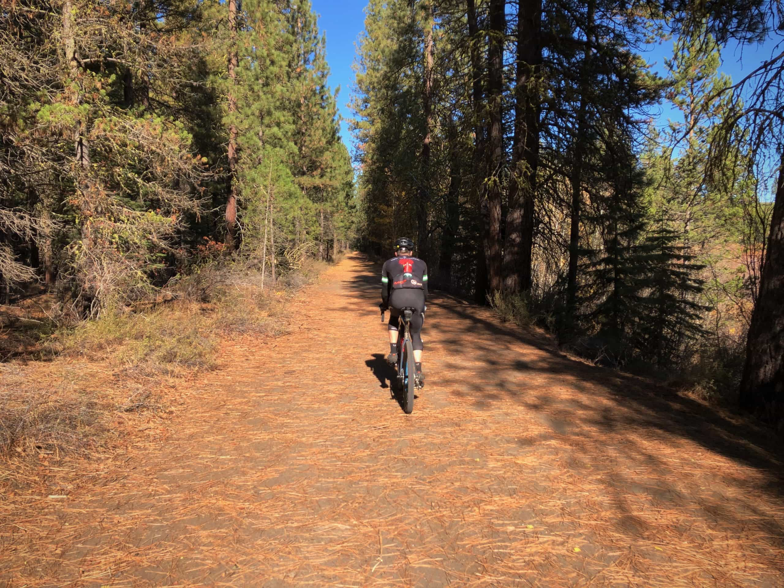 Gravel cyclist on paved path leading to Sunriver from Benham Falls.