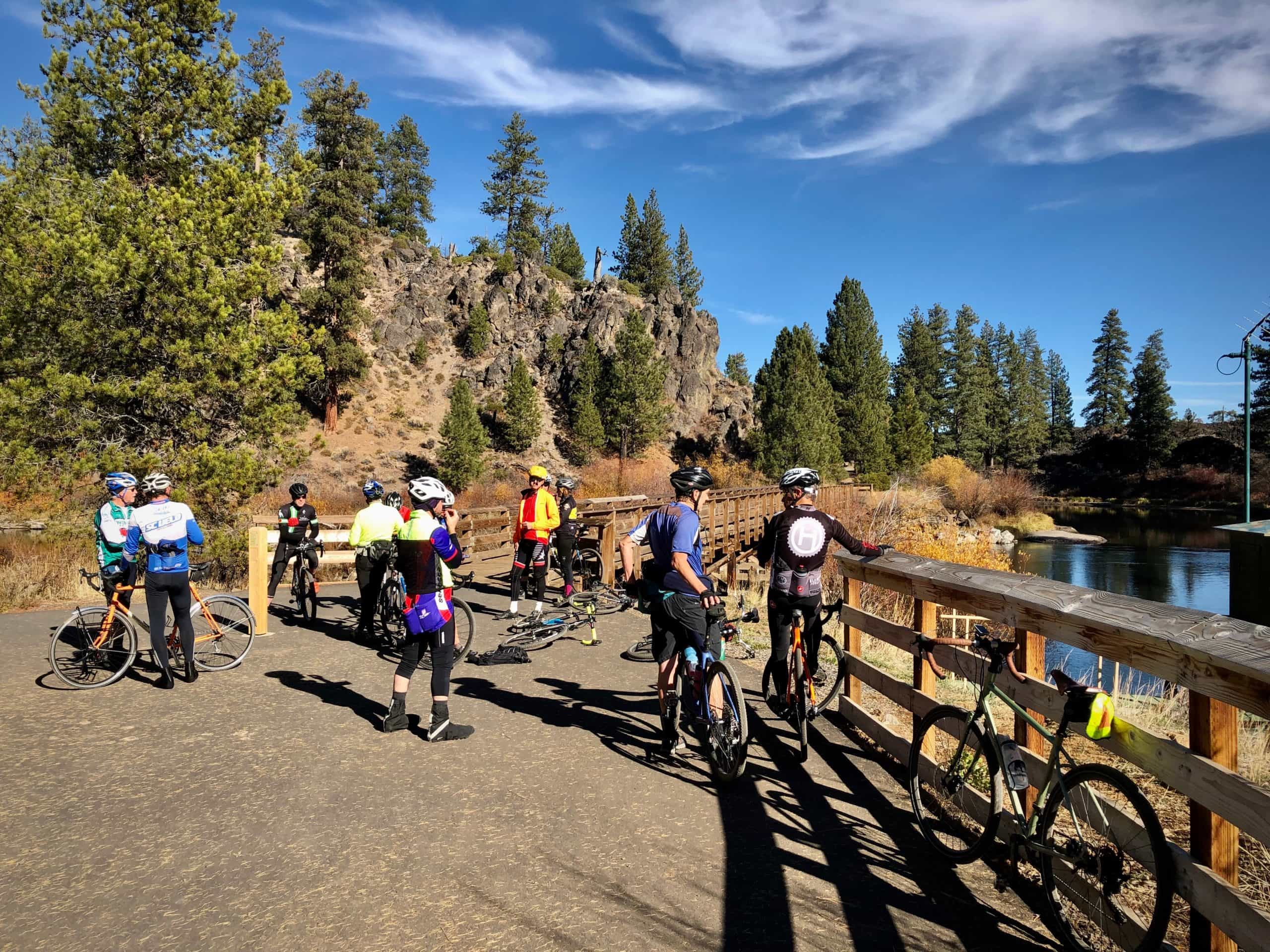 A group of gravel cyclists gathered on the wooden bridge at Benham Falls near Bend, Oregon.
