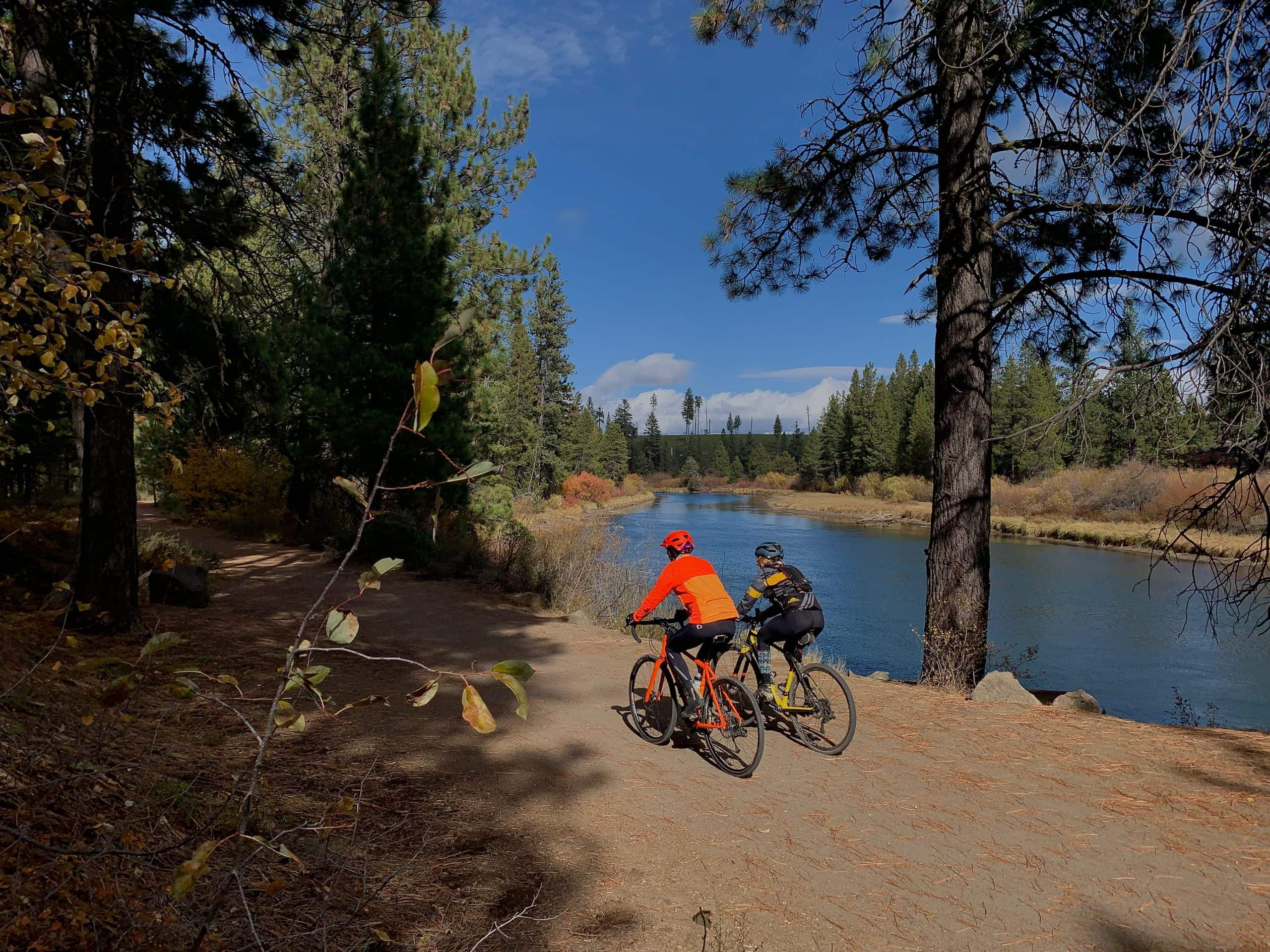 Two woman gravel cyclists on the dirt path between Benham Falls and the the wooden bridge near Sunriver, Oregon.