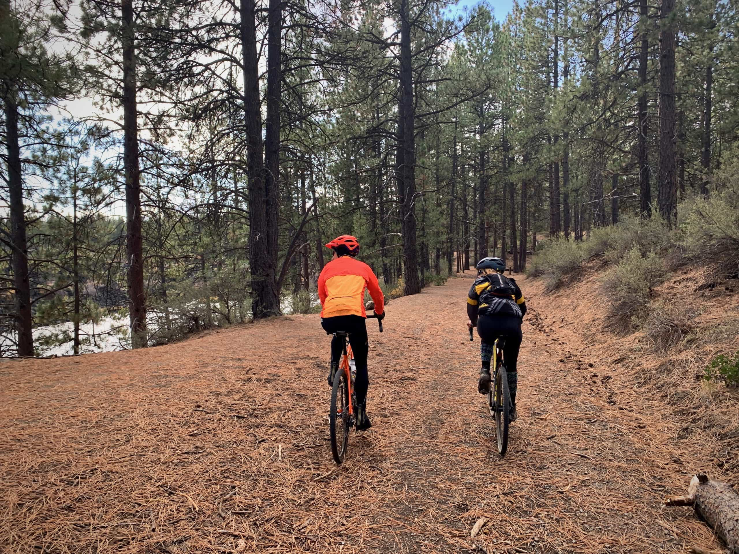 Two women cyclists riding double track on gravel bikes near the Deschutes River Trail near Bend, Oregon.