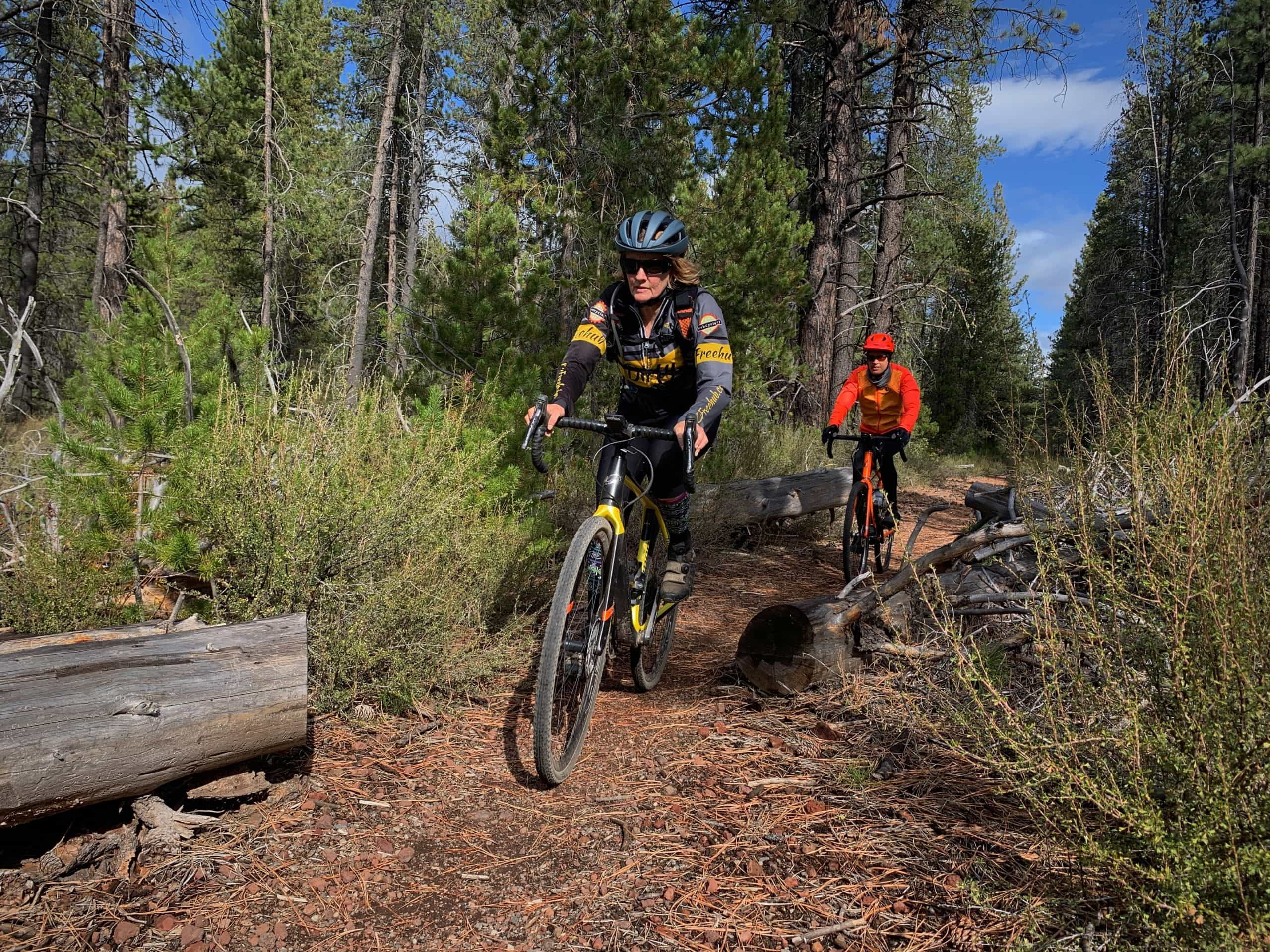 Two woman cyclist riding single track between downed trees near Benham Falls.