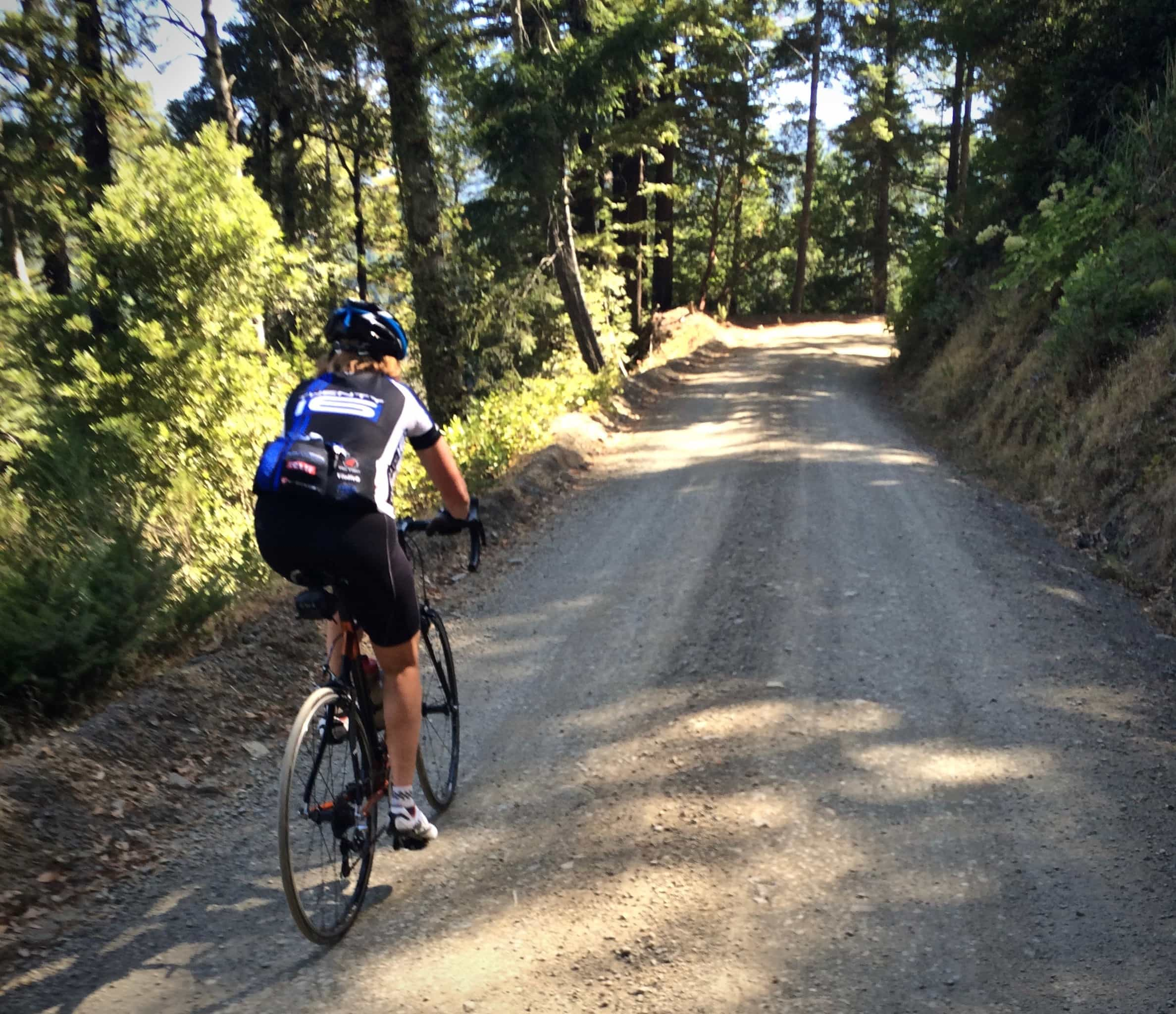 Cyclist on gravel road leading to Dyerville Loop road in Humboldt county, California.