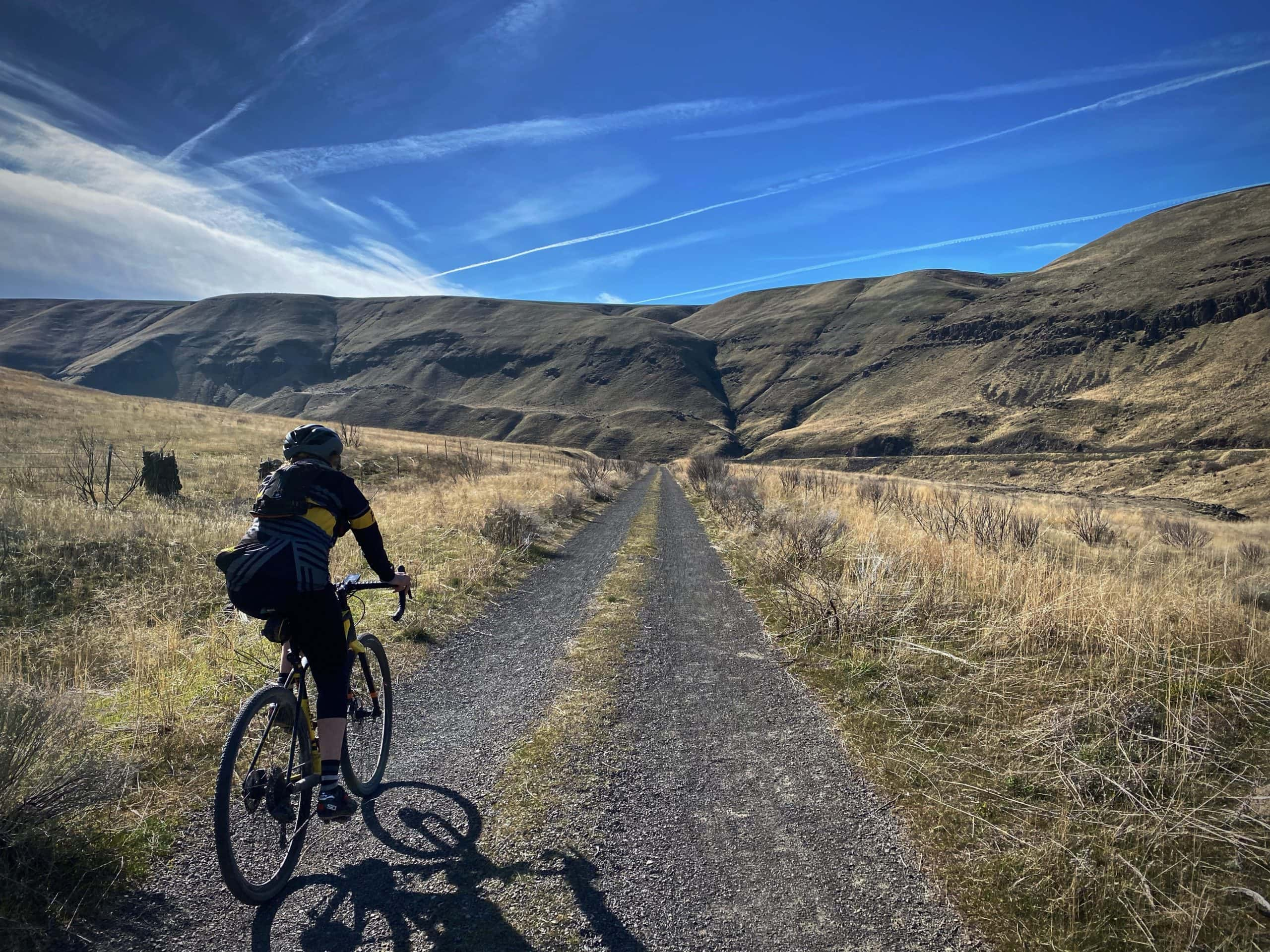Woman gravel cyclist on double track trail near the Deschutes River.
