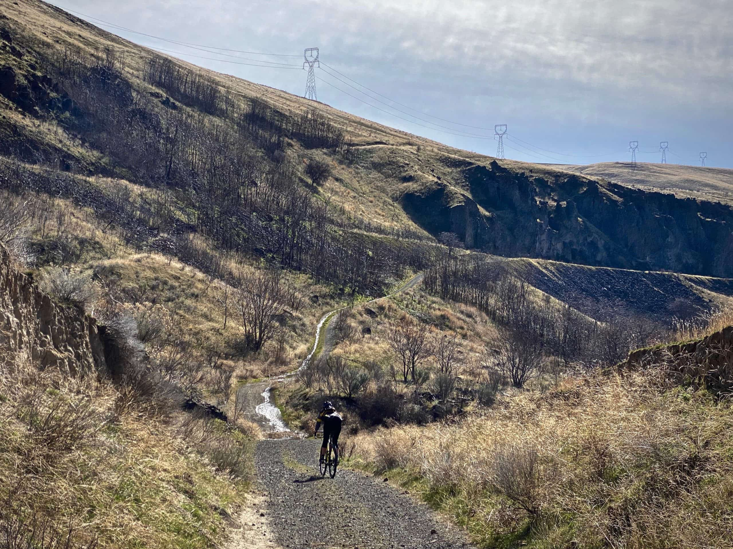 Cyclist dropping into a dip on the gravel trail along the Deschutes River.
