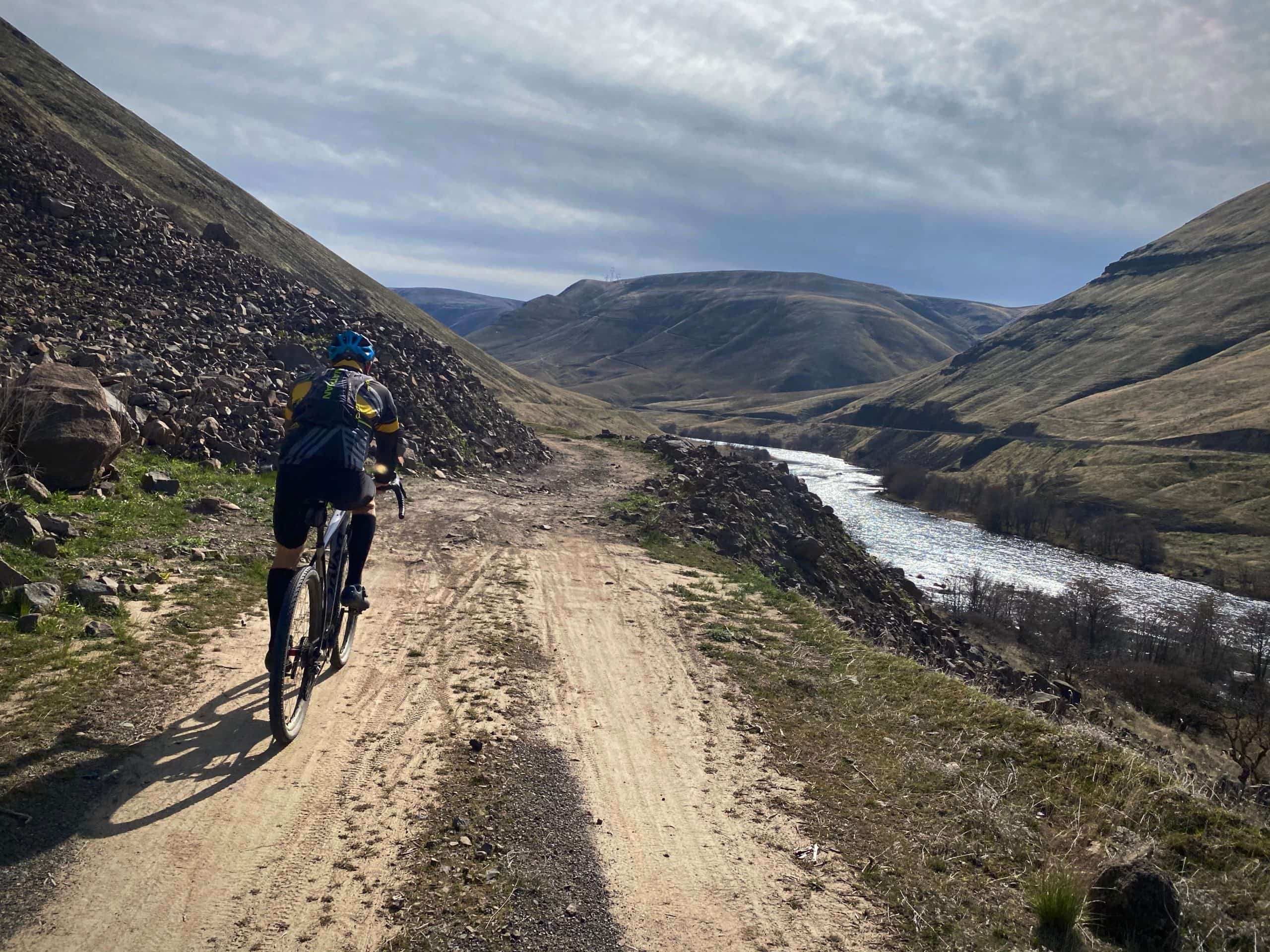 Gravel cyclist on double track trail along the Deschutes River near the Columbia River Gorge.