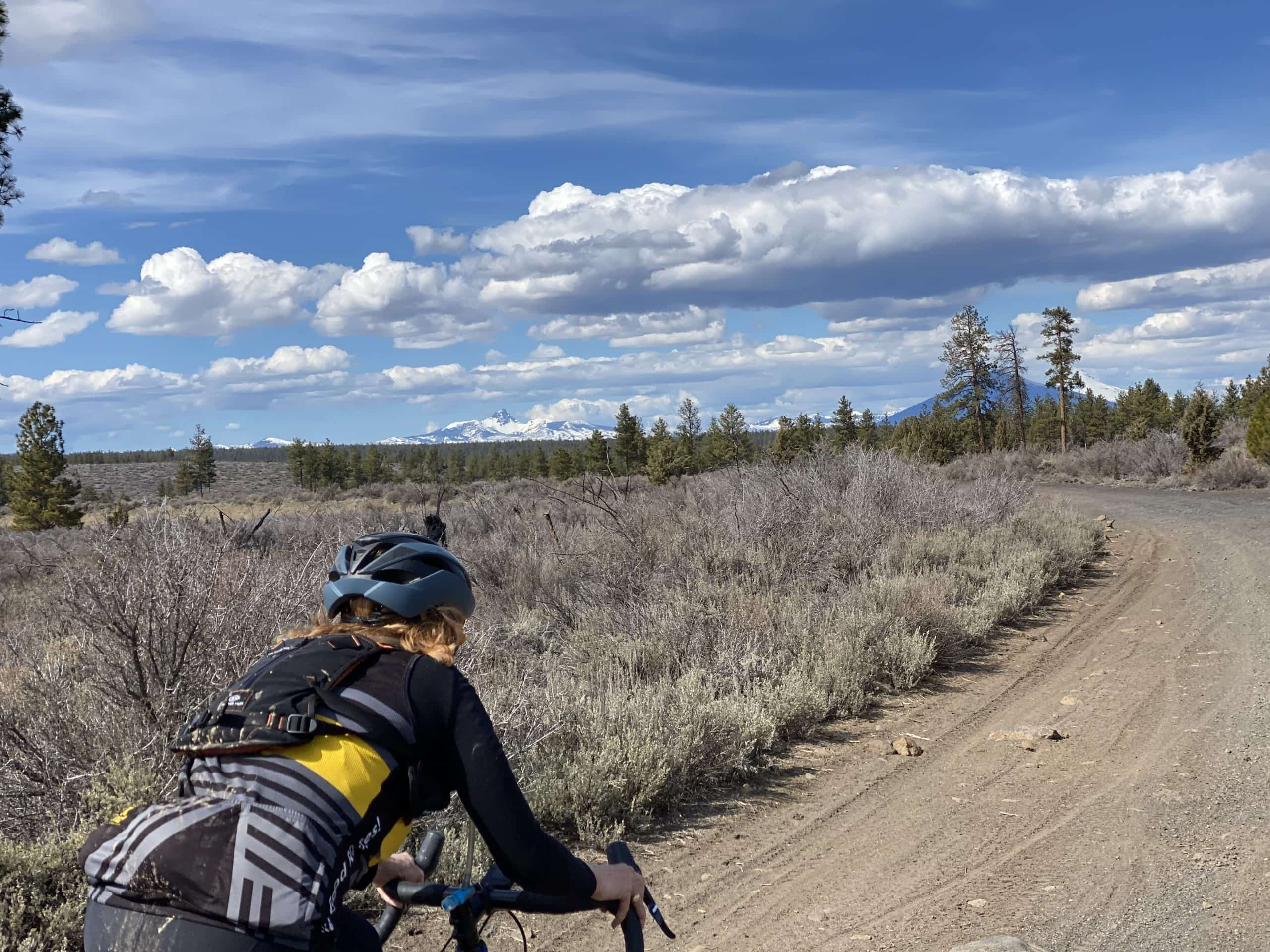 Gravel cyclist on dirt road with Mt Washington and Black Butte in the distance.