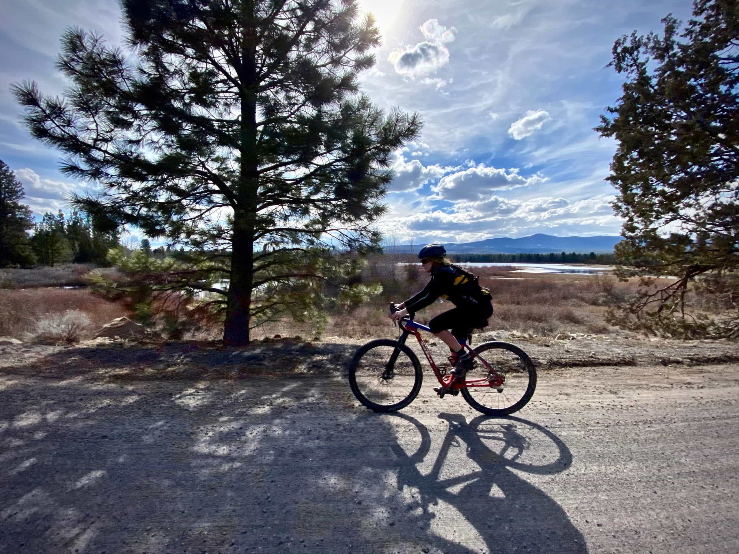 Cyclist riding past Tumalo Reservoir with bright colors near Bend, Oregon.