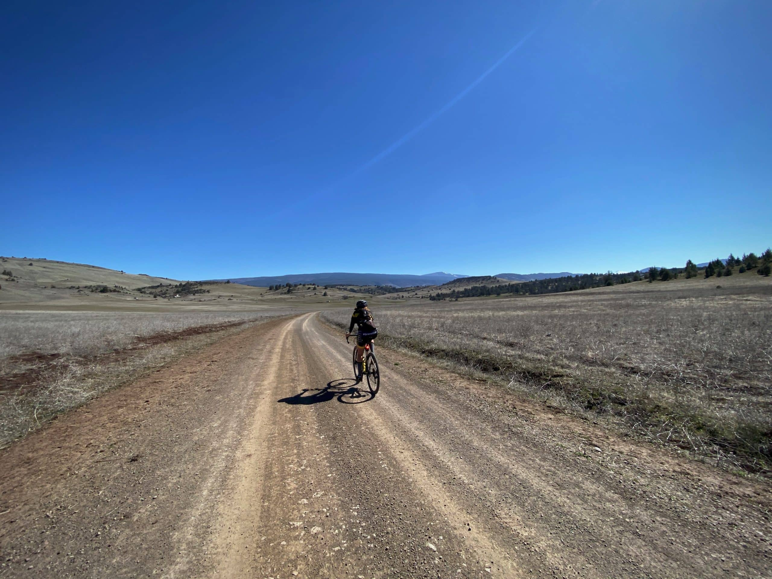 Cyclist on gravel roads with open view. Near Iron Gate reservoir and Copco lake. Yreka, CA.