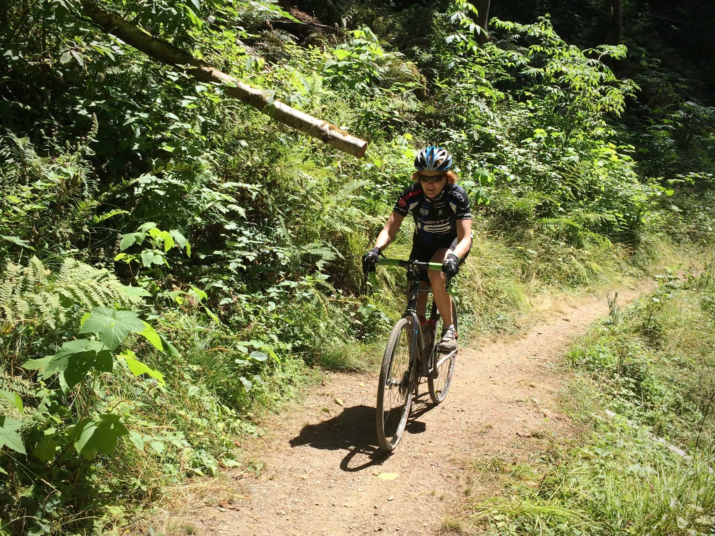 Gravel cyclist riding the single track of Streelow trail in Prairie Creek Redwoods state park in California, near Crescent City.