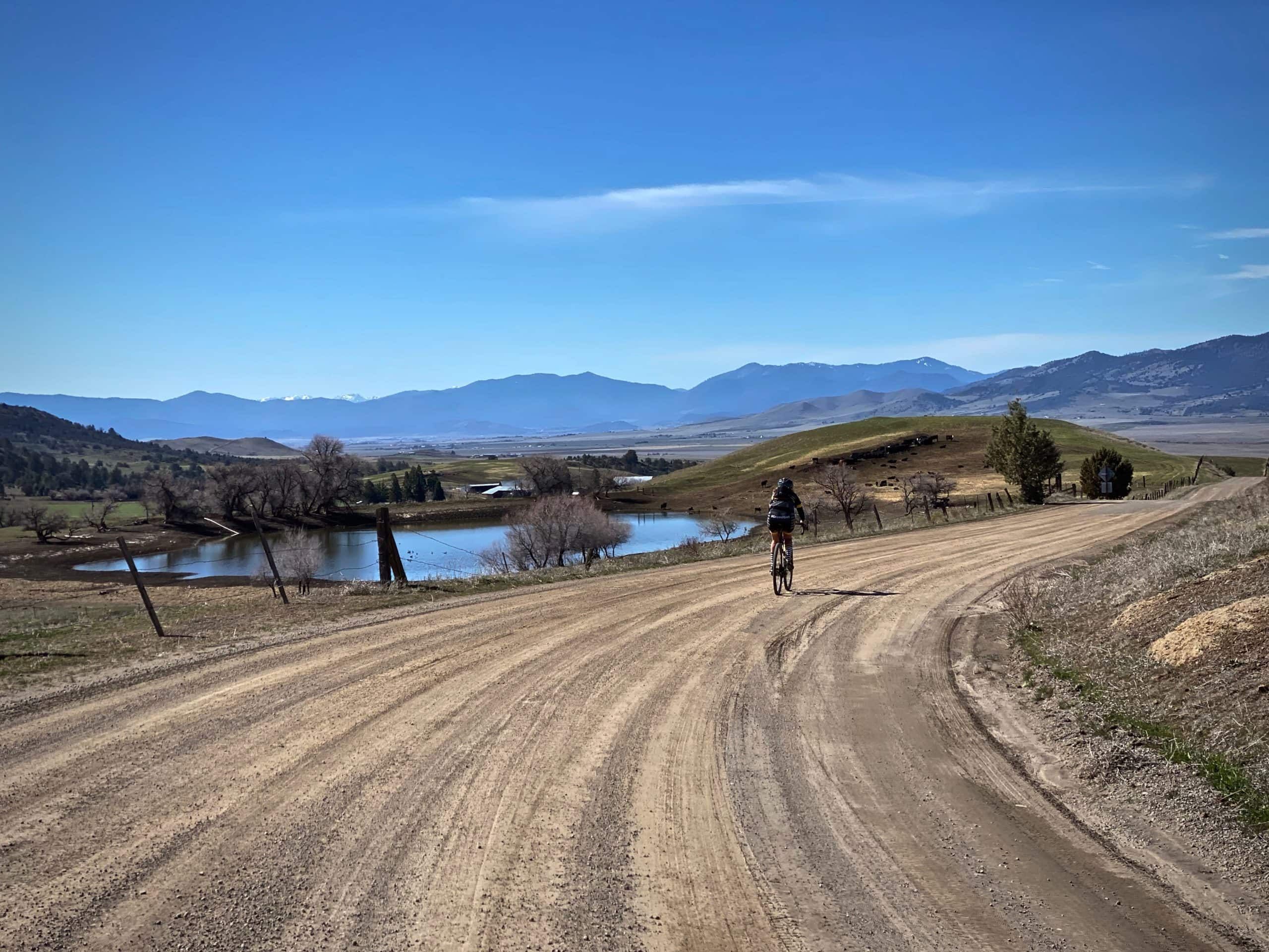 Woman gravel cyclist on gravel / dirt road heading south with Trinity mountains in the background.