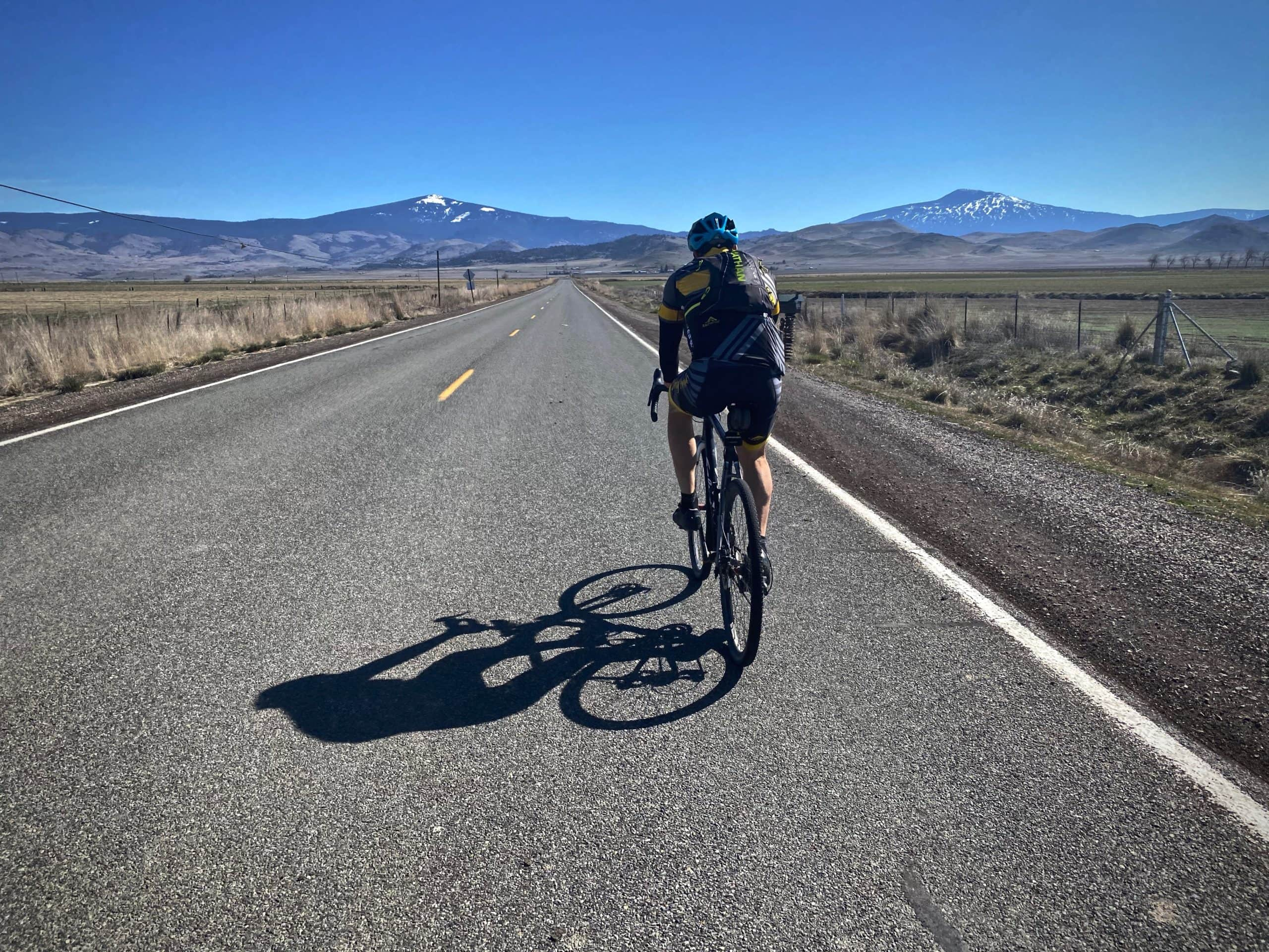 Woman cyclist on paved road heading north out of Montage, CA in northern California.