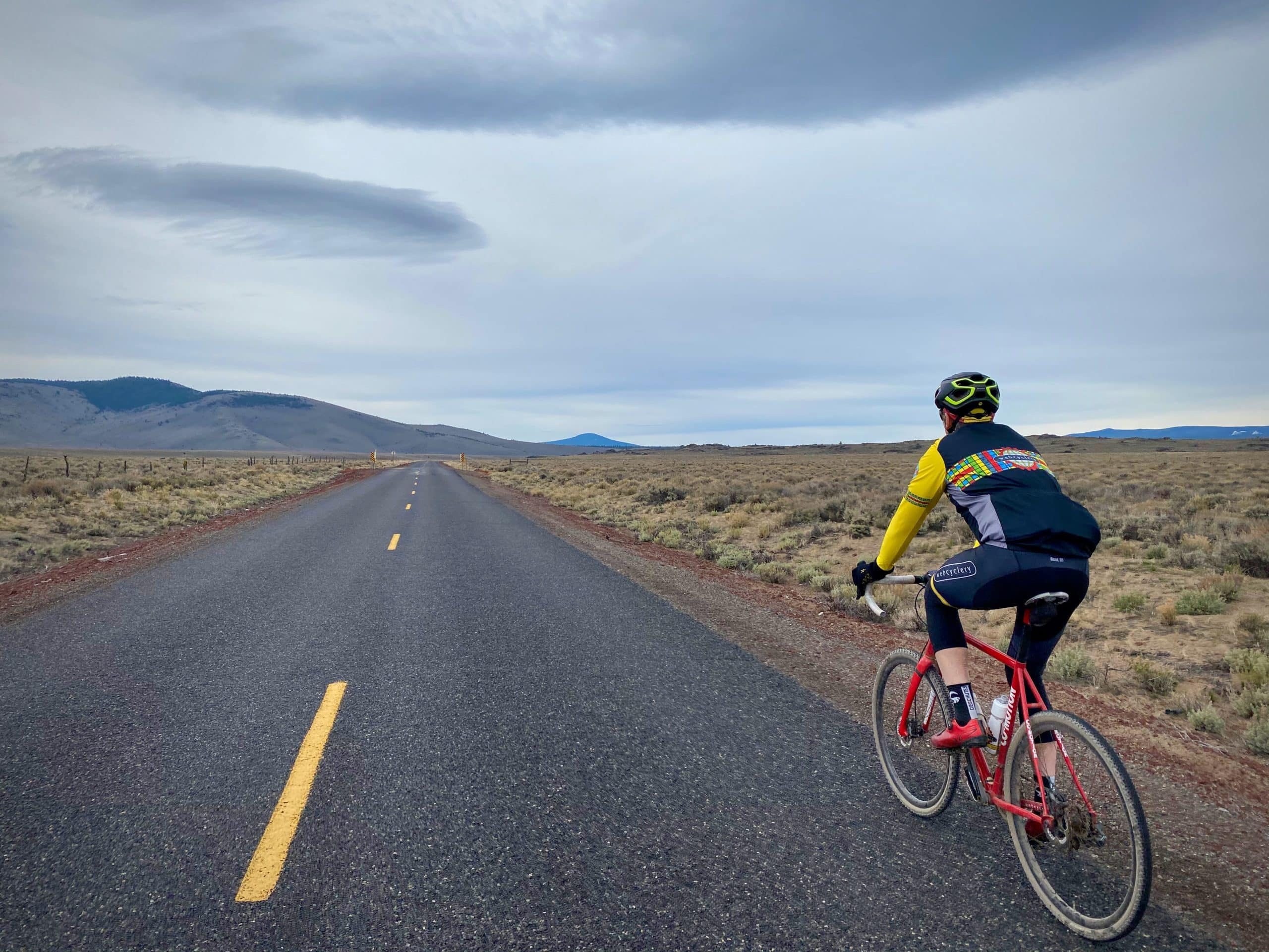 Cyclist on paved road in the Millican Valley near Bend, Oregon.