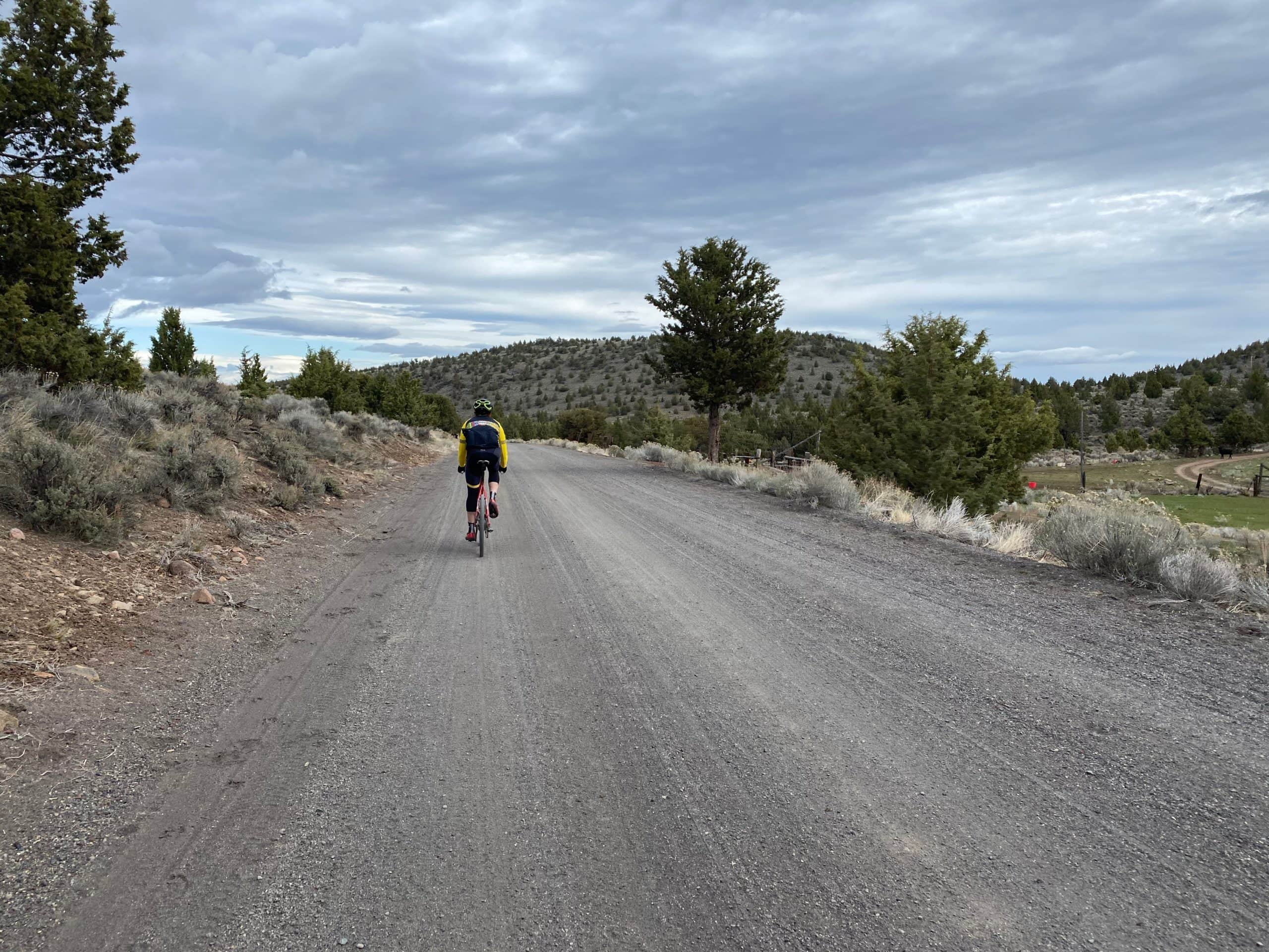 Cyclist riding Pine Mountain road towards Highway 20 near Bend, OR.