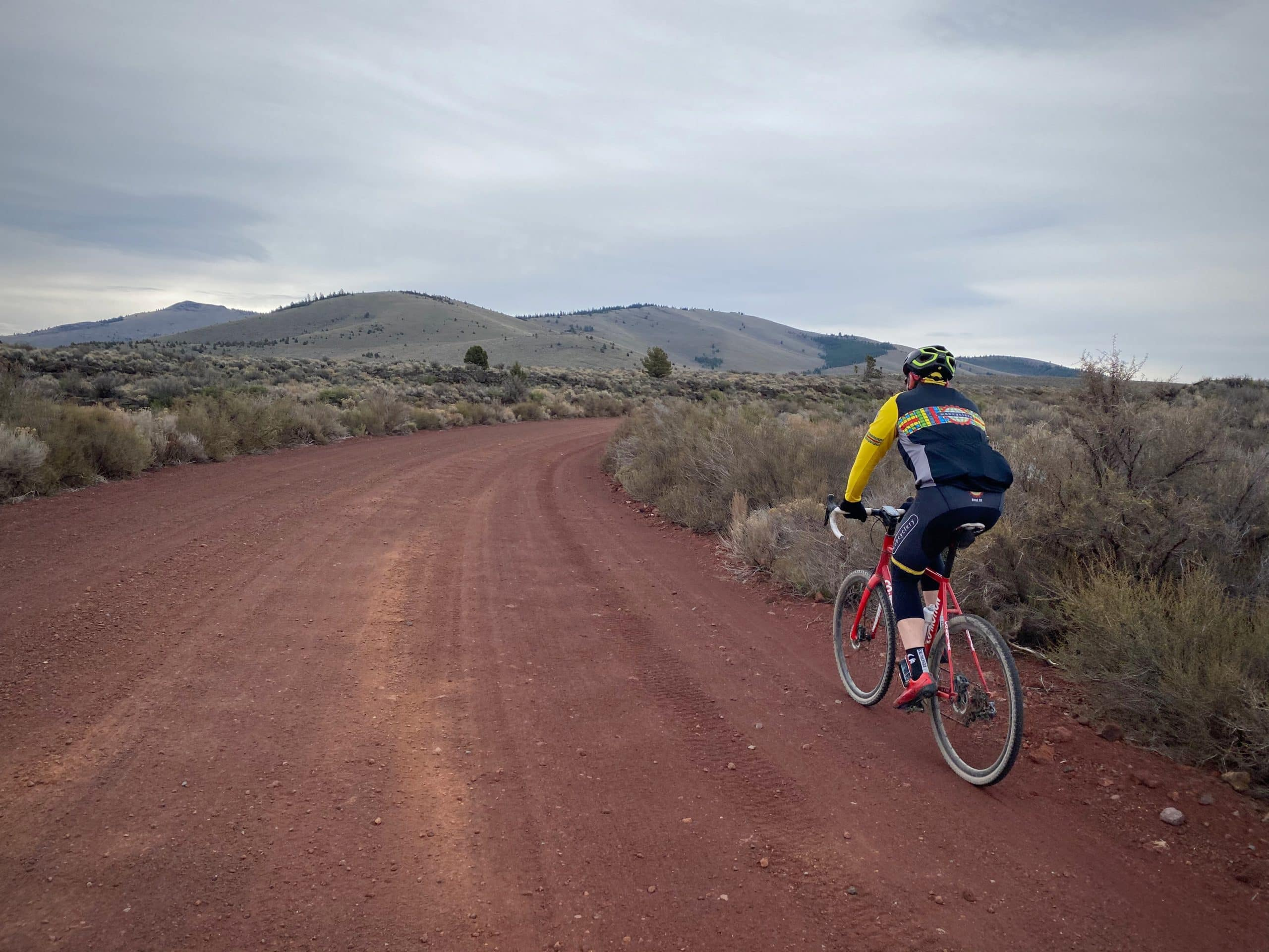 Cyclist on red cinder road near Pine Mountain, in Oregon.